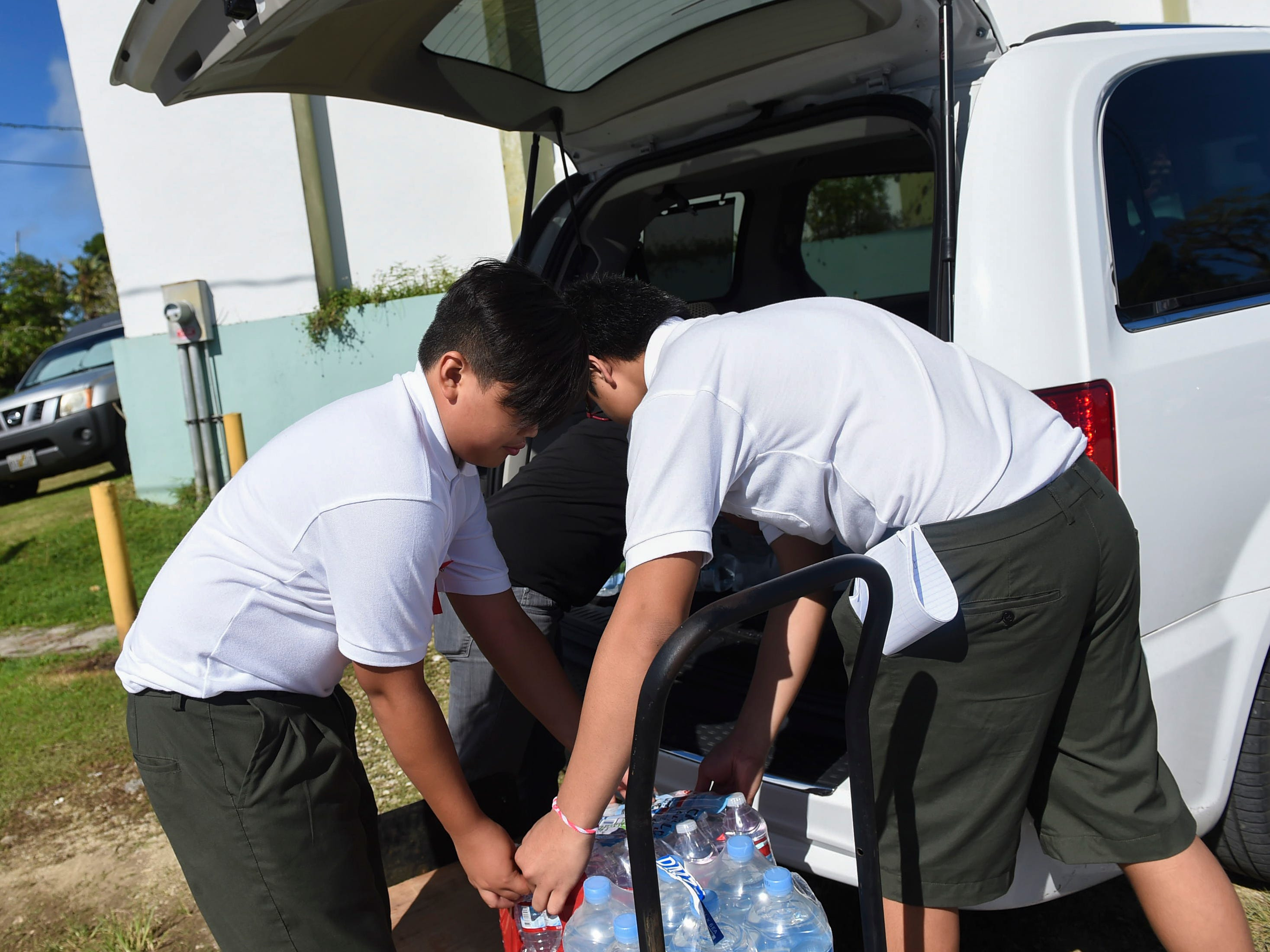 San Vicente Catholic School students Bryce Anthony Cruz Sablan, 12, left, and Brendon C. Santos Cellona 13, unload cases of bottled water for a Super Typhoon Yutu relief effort at the San Vicente Catholic School campus, Oct. 29, 2018.