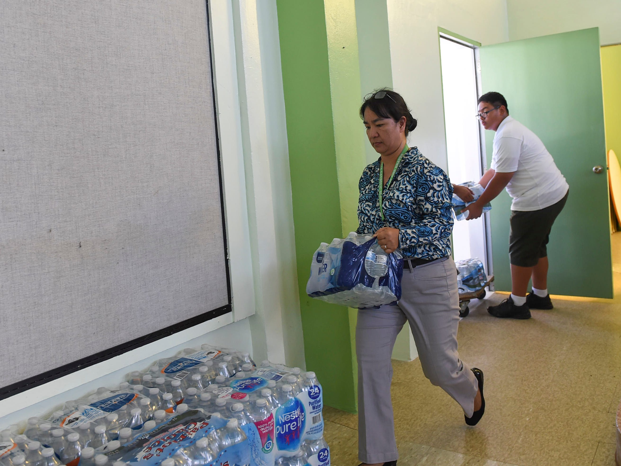 San Vicente Catholic School Principal Nelba R. Aquino carries a case of bottled water in the staging and distribution area for a Super Typhoon Yutu relief effort at her school's campus, Oct. 29, 2018.