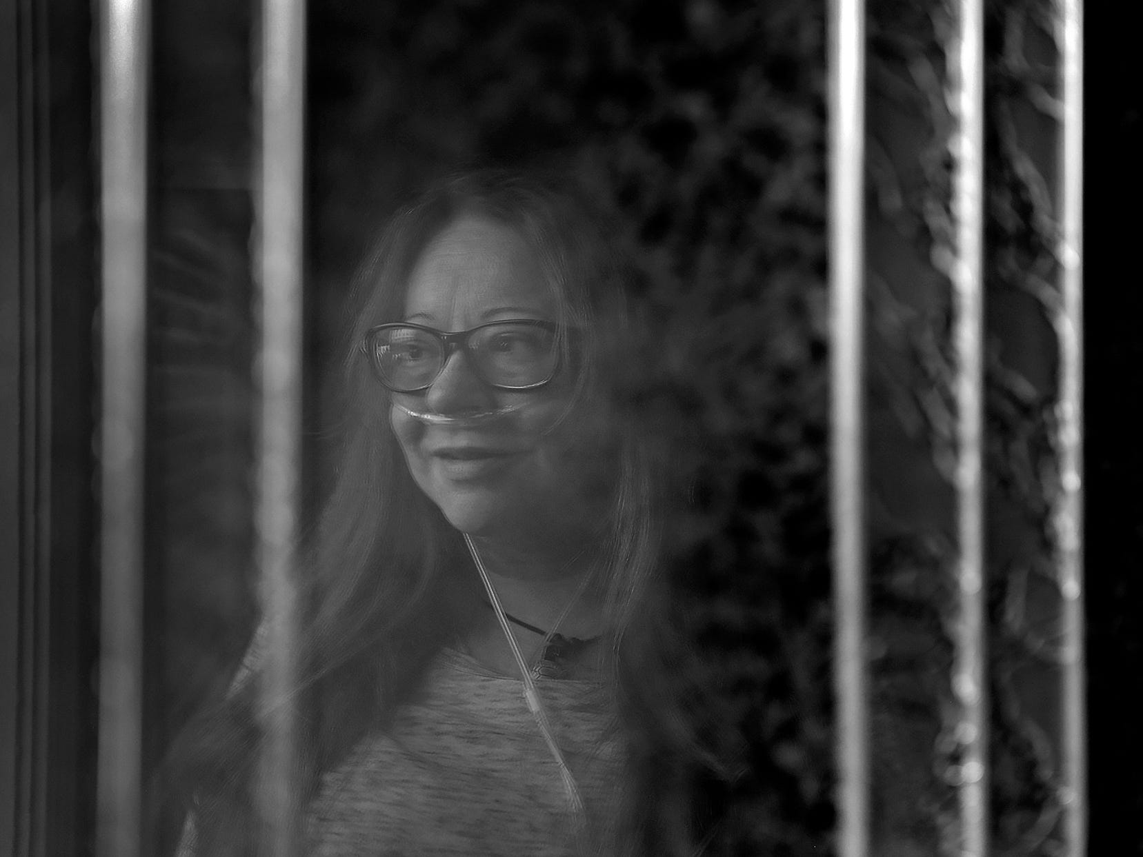 Sheri Medcalf is reflected in her patio door at her temporary home at the Abbie Hunt Bryce Home, Wednesday, June 13, 2018.  The home offers hospice for the dying poor.  It also offers a place to recuperate for Eskenazi patients who are homeless or poor, and need a little more help before going back to their lives.  Medcalf was an Eskenazi patient.