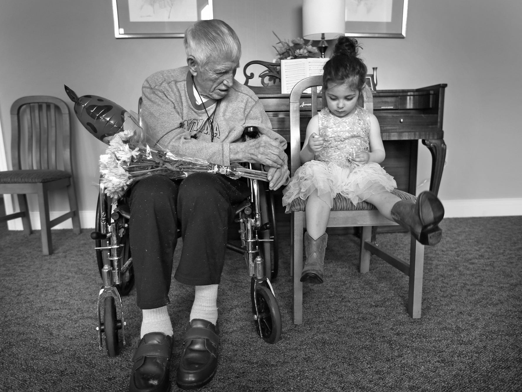 Dewey Logeland, left, and Julia Gonzalez, eat chocolate, as they visit at the Abbie Hunt Bryce Home, Friday, April 27, 2018.  The home offers hospice for the dying poor. Julia, whose mother works often at the home, shares a love of horses with Logeland.  She and her family visited him, and shared chocolate and flowers.