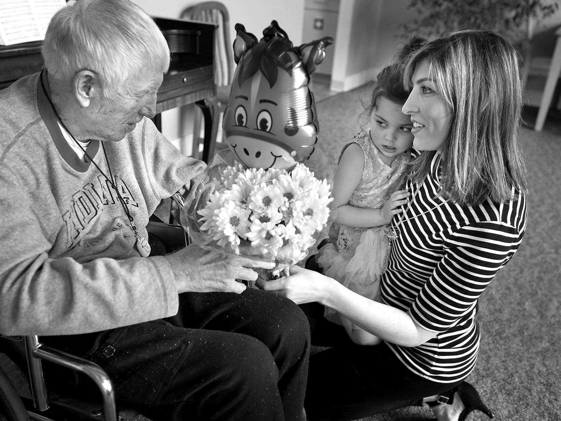 Dewey Logeland, left, meets Julia Gonzalez as she clings to her mother, Madison Gonzalez, at the Abbie Hunt Bryce Home, Friday, April 27, 2018.  The home offers hospice for the dying poor. Julia, whose mother works often at the home, shares a love of horses with Logeland.  The Gonzalez family visited Logeland, and shared chocolate and flowers.