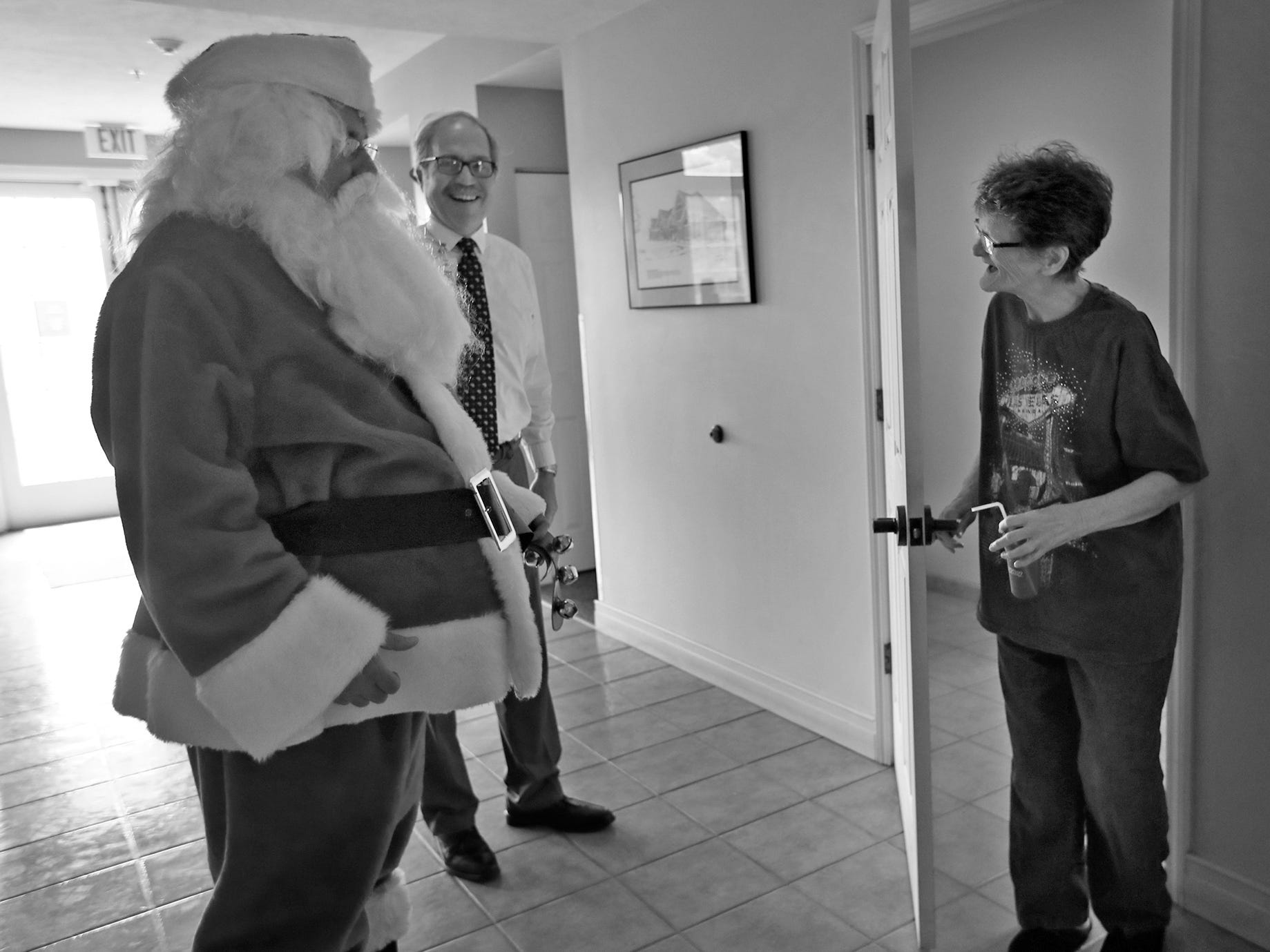 Resident Dixie Hinz, right, comes upon a surprise Santa, Matt Wilhelm, before the Christmas in July party at the Abbie Hunt Bryce Home, Wednesday, July 25, 2018.  The home offers hospice for the dying poor.  Tom Fodor, CEO and Executive Director of Morning Light, center, laughs along.