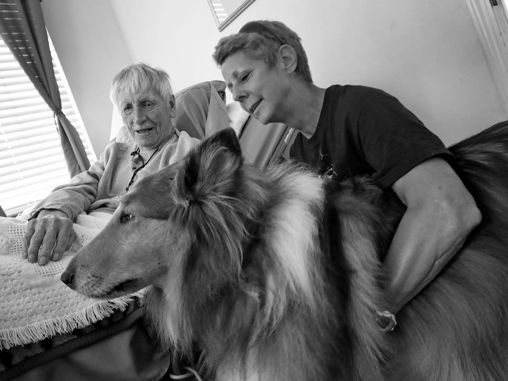 Marie Koenig, right, and Sir Willis visit with Dewey Logeland at the Abbie Hunt Bryce Home, Friday, Sept. 21, 2018.  The home offers hospice for the dying poor. Logeland moved to the home in 2018.