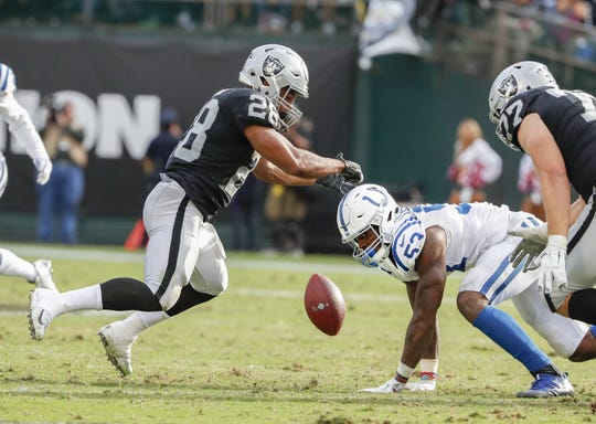 Indianapolis Colts linebacker Darius Leonard (53) forces a fumble on Oakland Raiders running back Doug Martin (28).