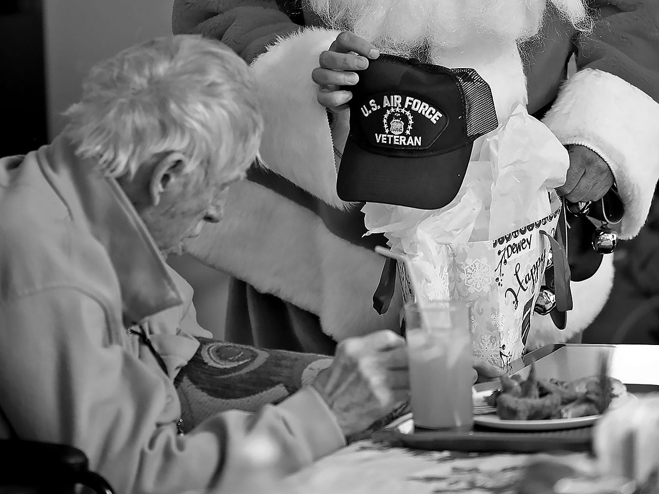 Santa, played by Matt Wilhelm, gives a present to Dewey Logeland during the Christmas in July party at the Abbie Hunt Bryce Home, Wednesday, July 25, 2018.  The present is an Air Force veteran hat.  The home offers hospice for the dying poor.