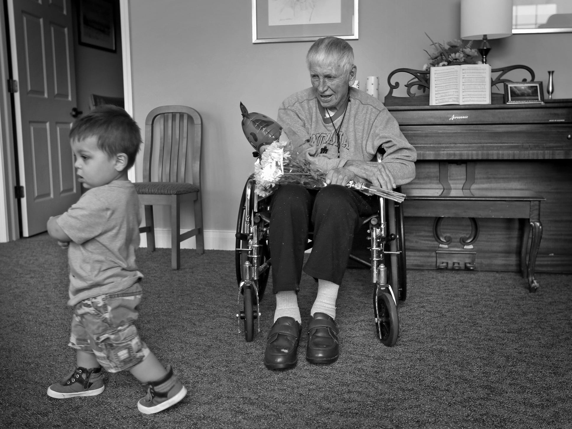 Dewey Logeland, right, smiles as Bennett Gonzalez runs by, as the Gonzalez family visits at the Abbie Hunt Bryce Home, Friday, April 27, 2018.  The home offers hospice for the dying poor.