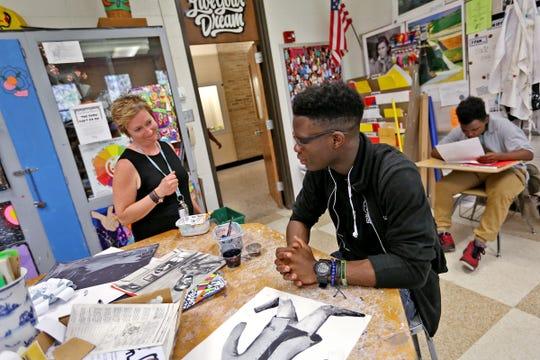 Northwest High School art and ceramics teacher Kim Dax (left) talks with student Abiodun Akinseye on May 7, 2018.