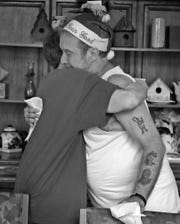 Dixie Hinz, left, and Richard Duarte hug in a tearful moment during the Christmas in July party at the home, Wednesday, July 25, 2018.  They are both residents at the home that offers hospice for the dying poor. Duarte died Oct. 14, 2018.