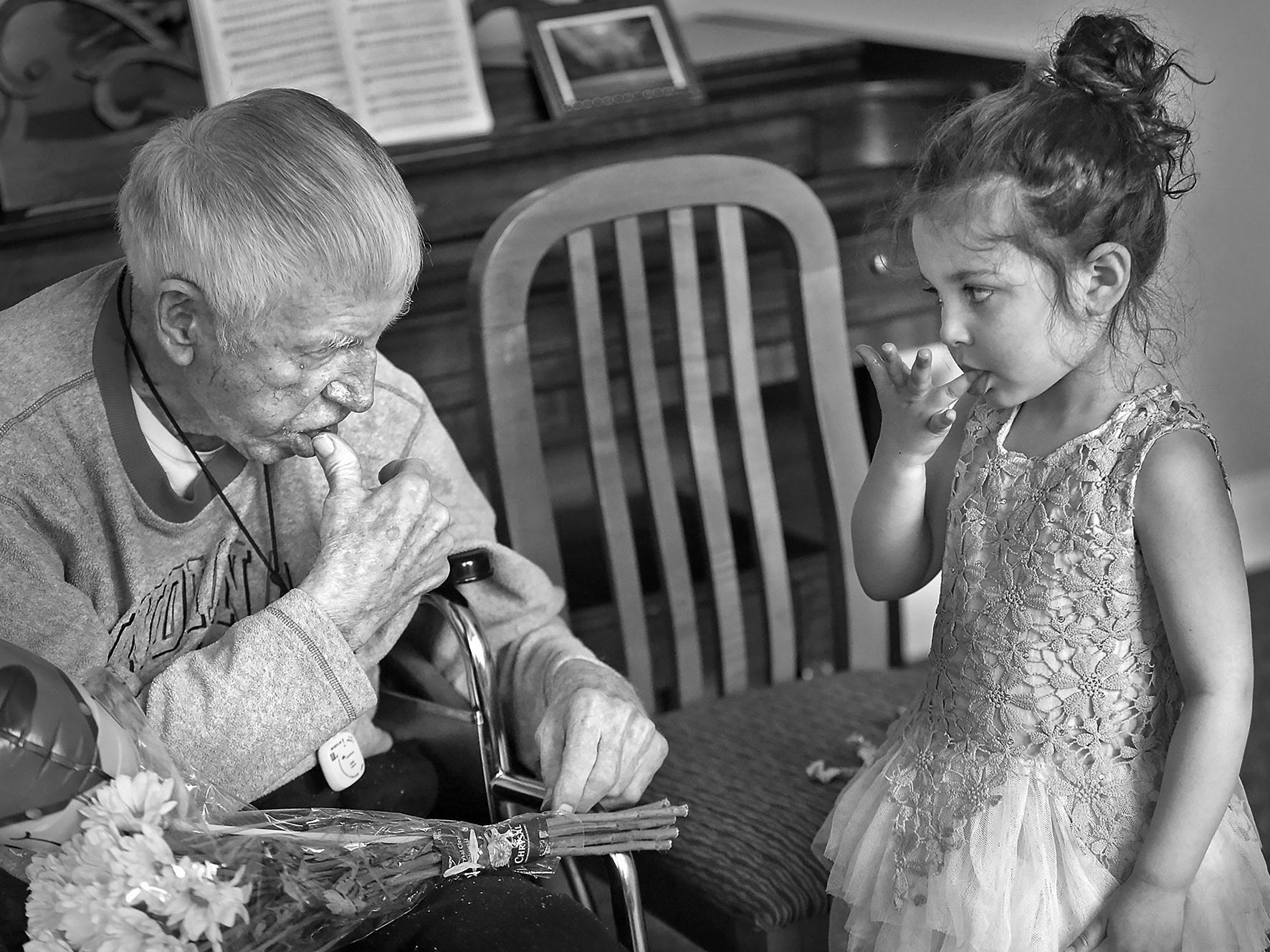 Dewey Logeland, left, and Julia Gonzalez, lick their chocolatey fingers, as they visit at the Abbie Hunt Bryce Home, Friday, April 27, 2018.  The home offers hospice for the dying poor. Julia, whose mother works often at the home, shares a love of horses with Logeland.  She and her family visited him, and shared chocolate and flowers.