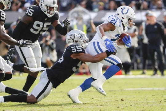 Indianapolis Colts running back Nyheim Hines (21) works to gain more yardage as he's pulled down by Oakland Raiders linebacker Marquel Lee.