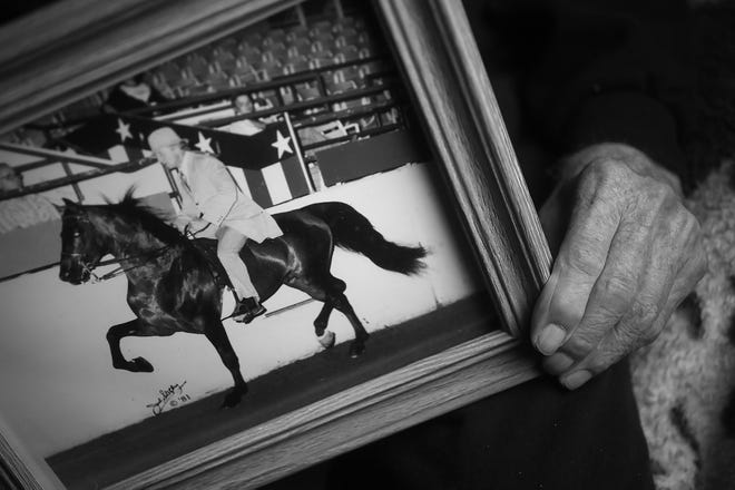 Dewey Logeland shows a photo of when he used to show horses, as he sits in his room at the Abbie Hunt Bryce Home, Friday, April 20, 2018.  The home offers hospice for the dying poor.