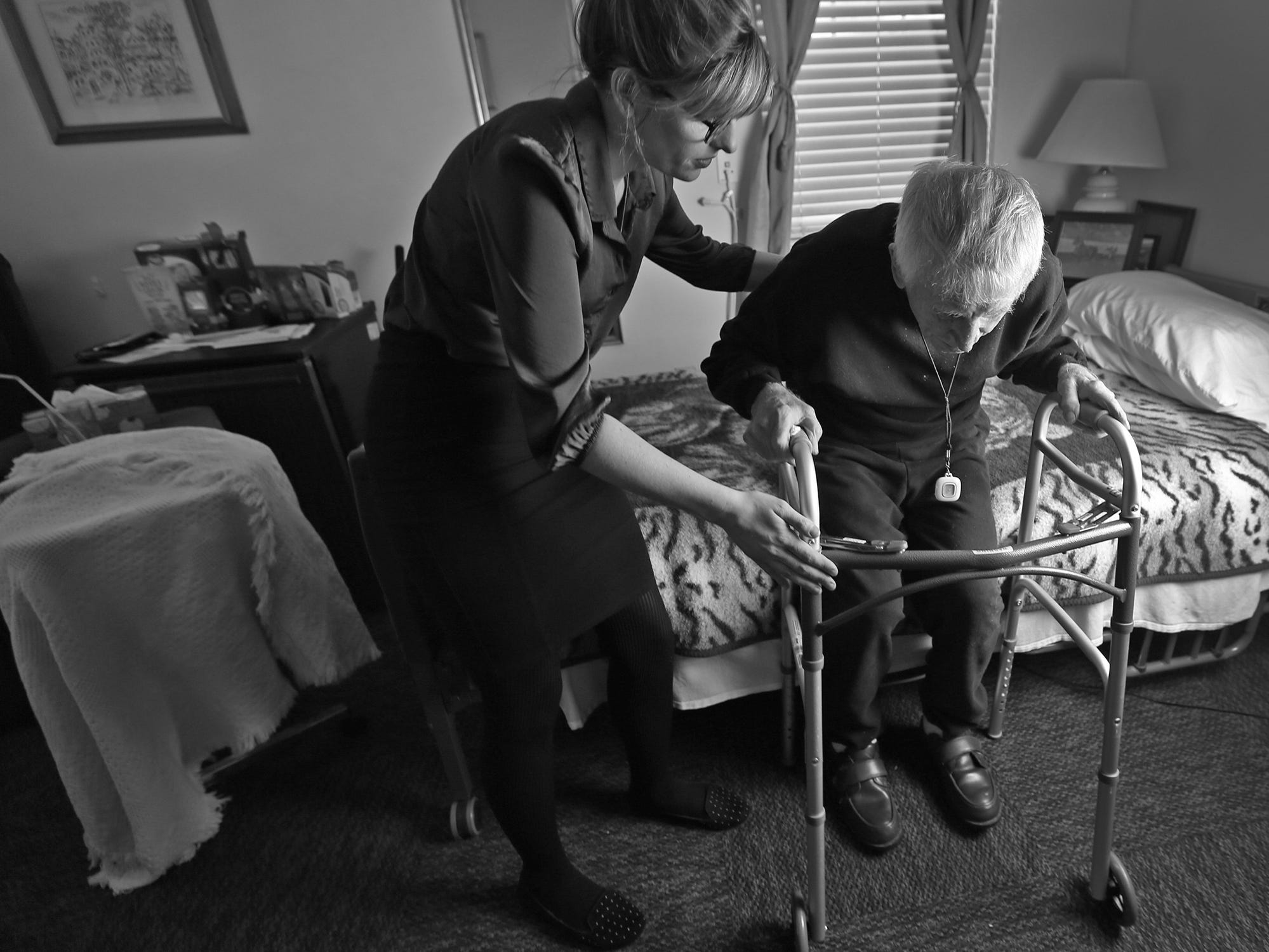 Madison Gonzalez, Morning Light's Community Involvement and Event Manager, left, helps Dewey Logeland in his room at the Abbie Hunt Bryce Home, Friday, April 20, 2018.  The home offers hospice for the dying poor.