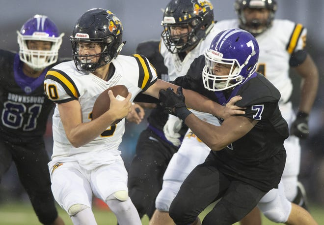 Brownsburg's Cameron Keys (7) grabs hold of Avon quarterback Henry Hesson during the Bulldogs' win over their Hendricks County rivals Sept. 7. They meet again in Friday's sectional final.