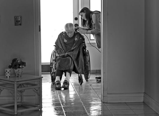 Dewey Logeland, left, gets his hair cut by Mallory Hook at the Abbie Hunt Bryce Home, Friday, April 27, 2018.  The home offers hospice for the dying poor.