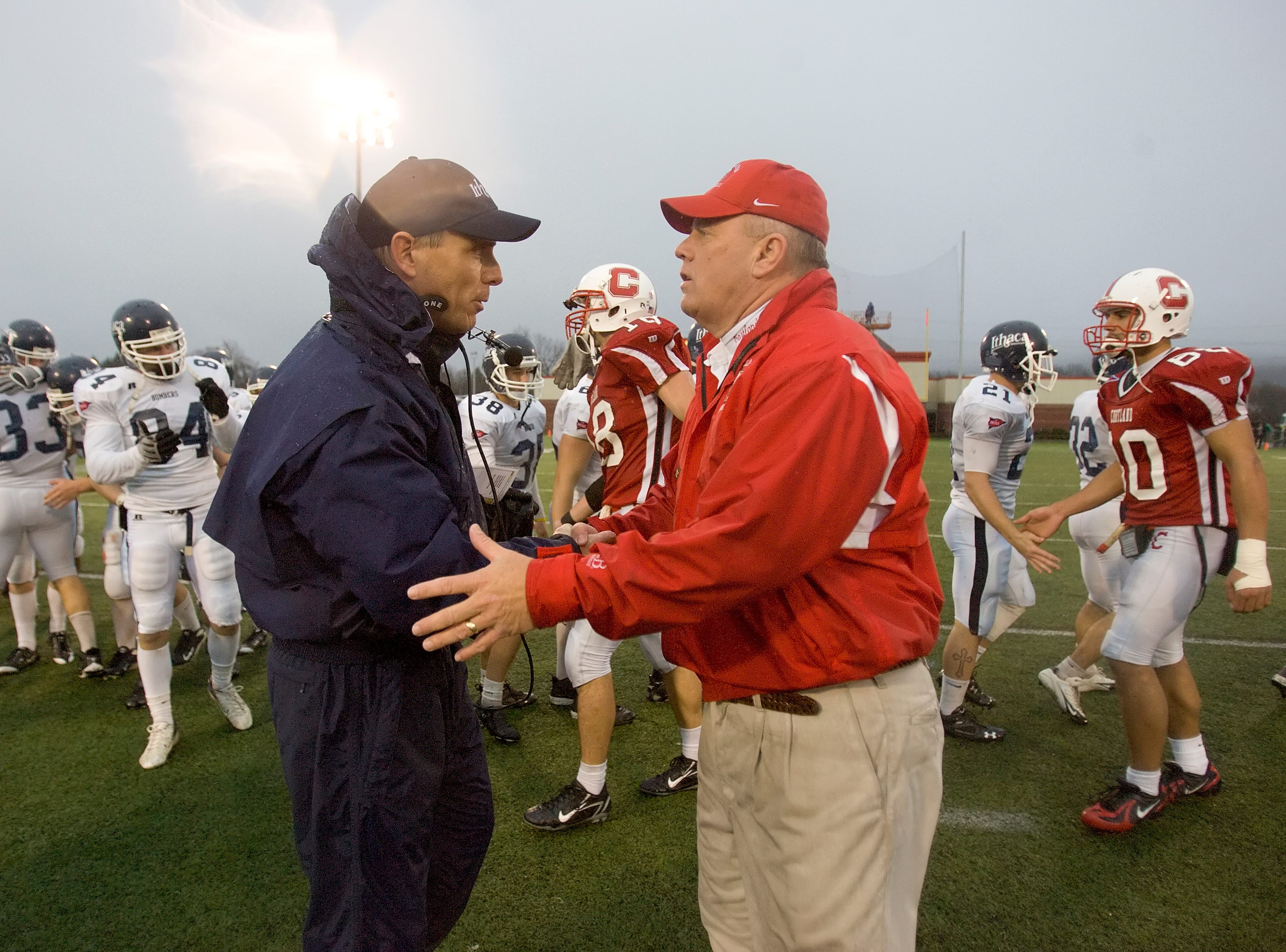 2009: SUNY Cortland head coach Dan MacNeill, right, congratulates Ithaca defensive coordinator Mark Ross at the conclusion of the 2008 Cortaca Jug game at Cortland. The two teams will play at noon Saturday at sold out Butterfield Stadium.