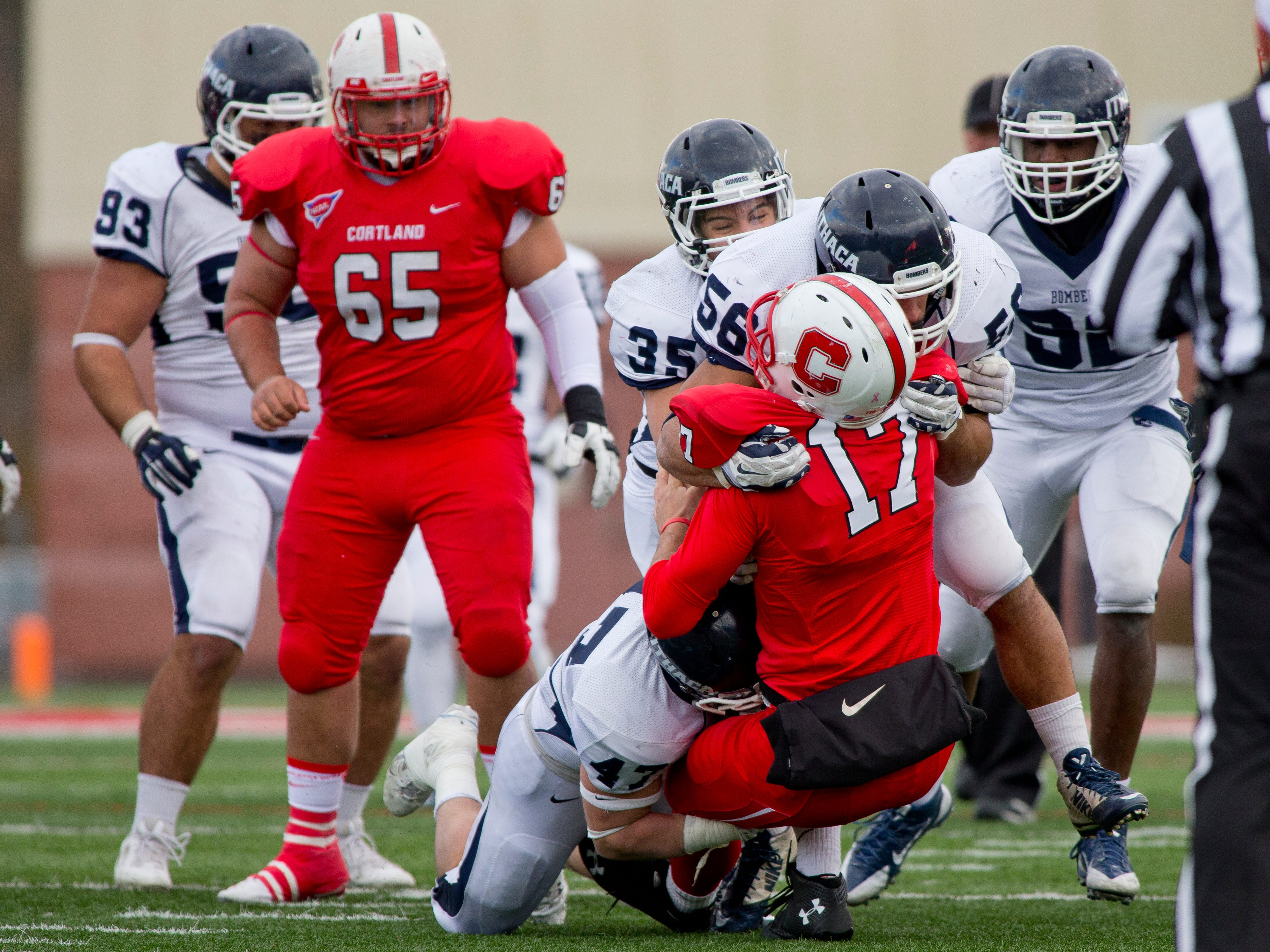 2014: The Ithaca defense takles Cortland's Lou Buschi Saturday during the Cortaca Jug game in Cortland.