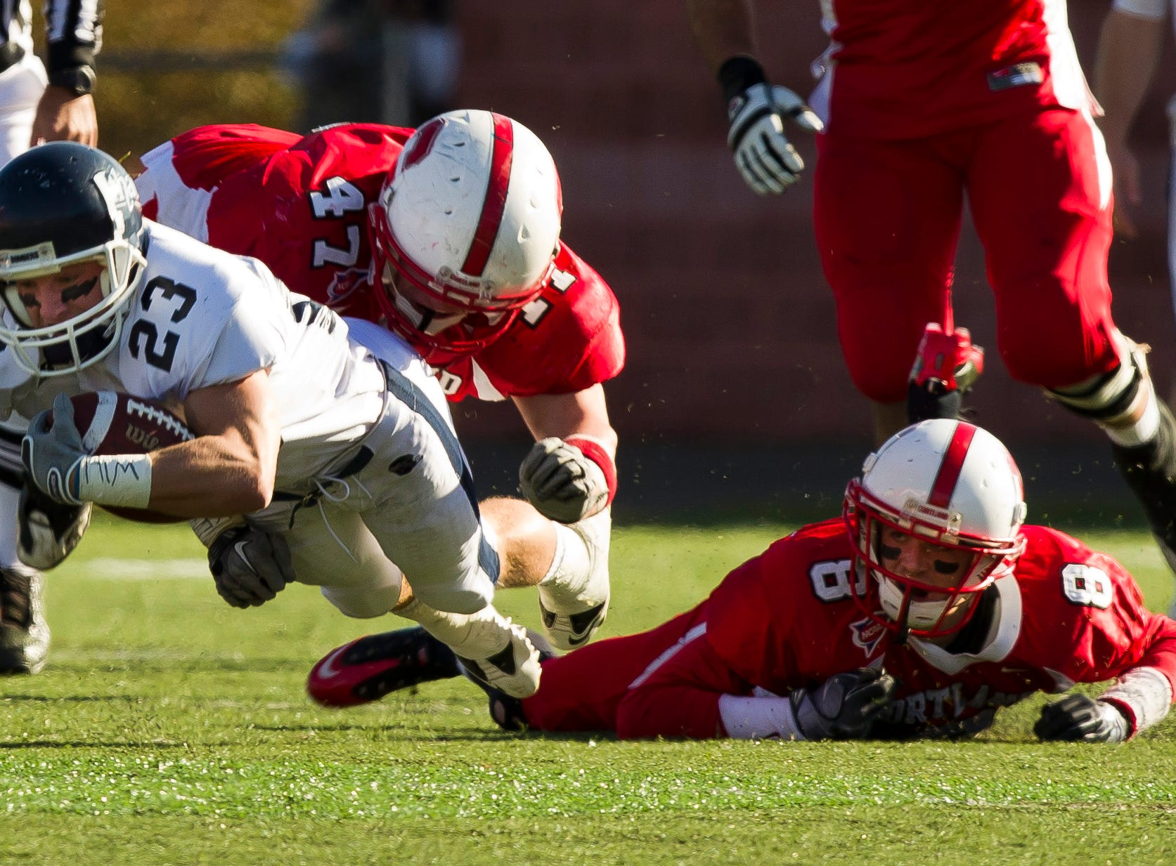 2010: Ithaca College's Dan Ruffrage is tackled by SUNY Cortland's Bill Smith as Cortland's Phil Bossman looks on during Saturday's Cortaca Jug in Cortland.