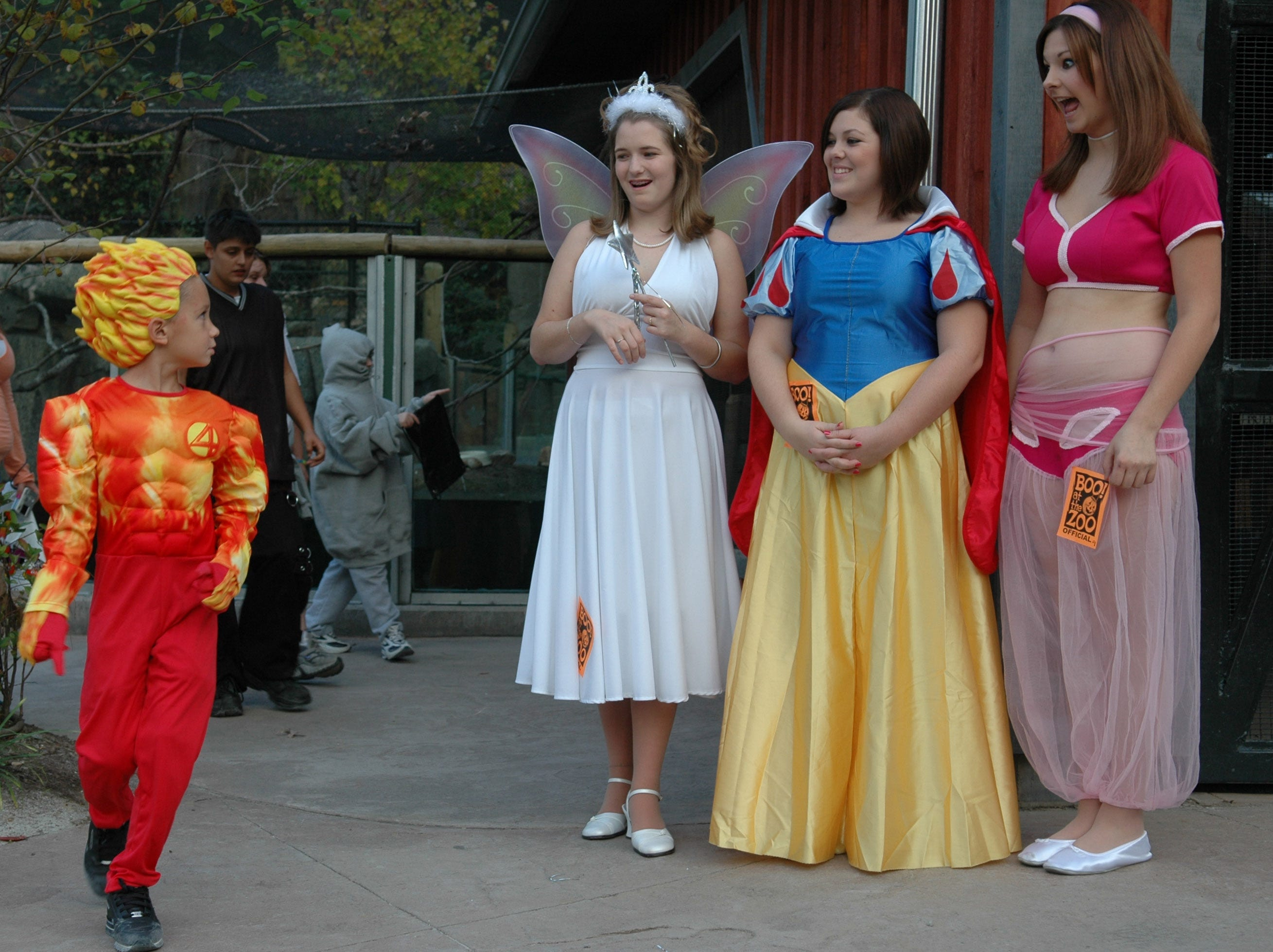 Justin Hurst, 6, of Knoxville, dressed in his Human Torch halloween costume, is surprised as he rounds the corner to be greeted by volunteers (from left), Julie Wood dressed as the fairy godmother, Kayla Shoffner dressed as Snow White, and Chason Washam, dressed as Jeannie while visiting the Knoxville Zoo for Boo at the Zoo Thursday night. 10/21/2005.