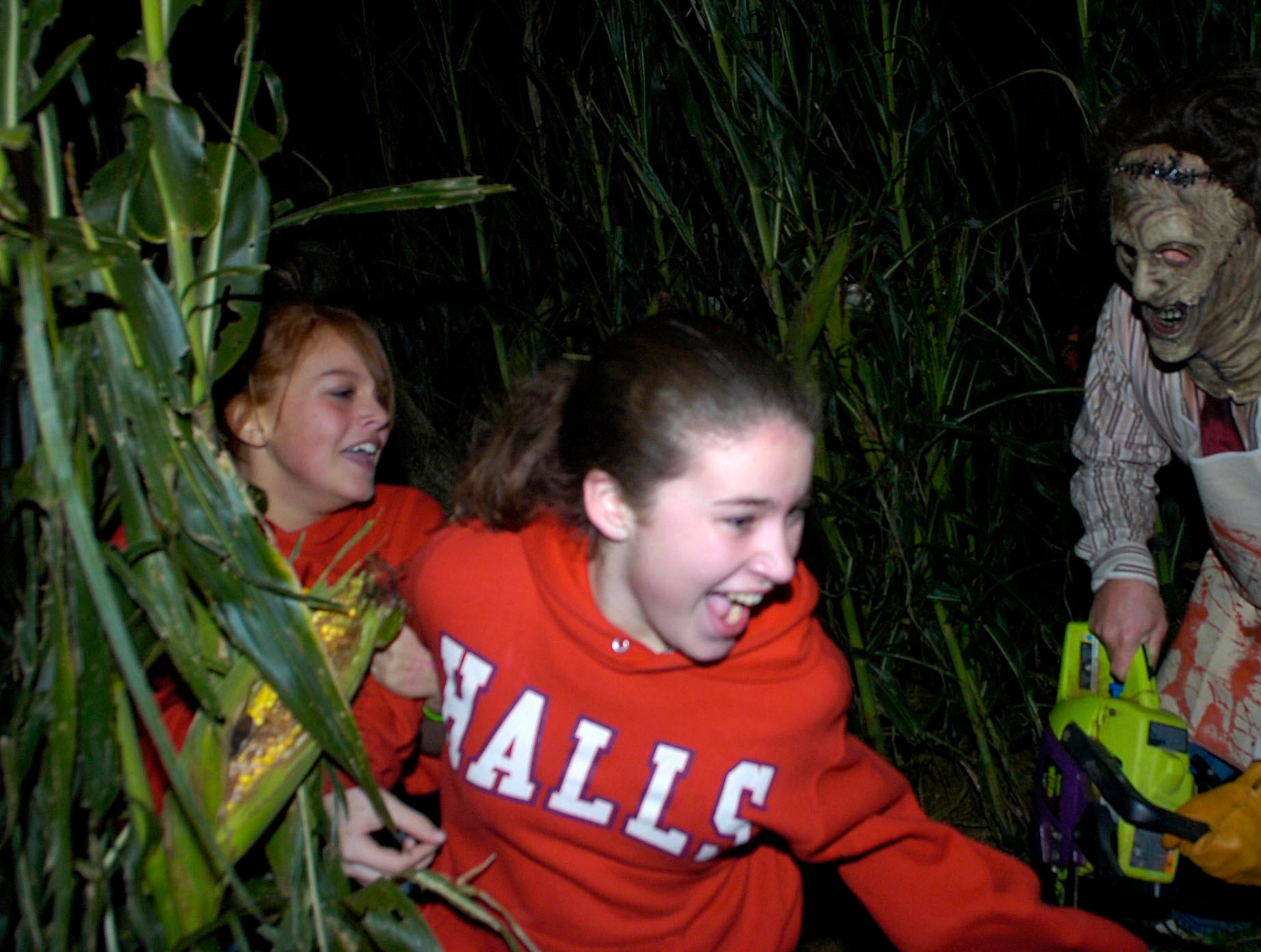 "Jasmine Andaluz (left) and Cheyanne DeBord of Halls try to run past a haunter at the ""Trail of Doom"" haunted corn maze on the Oakes Farm in Corryton."