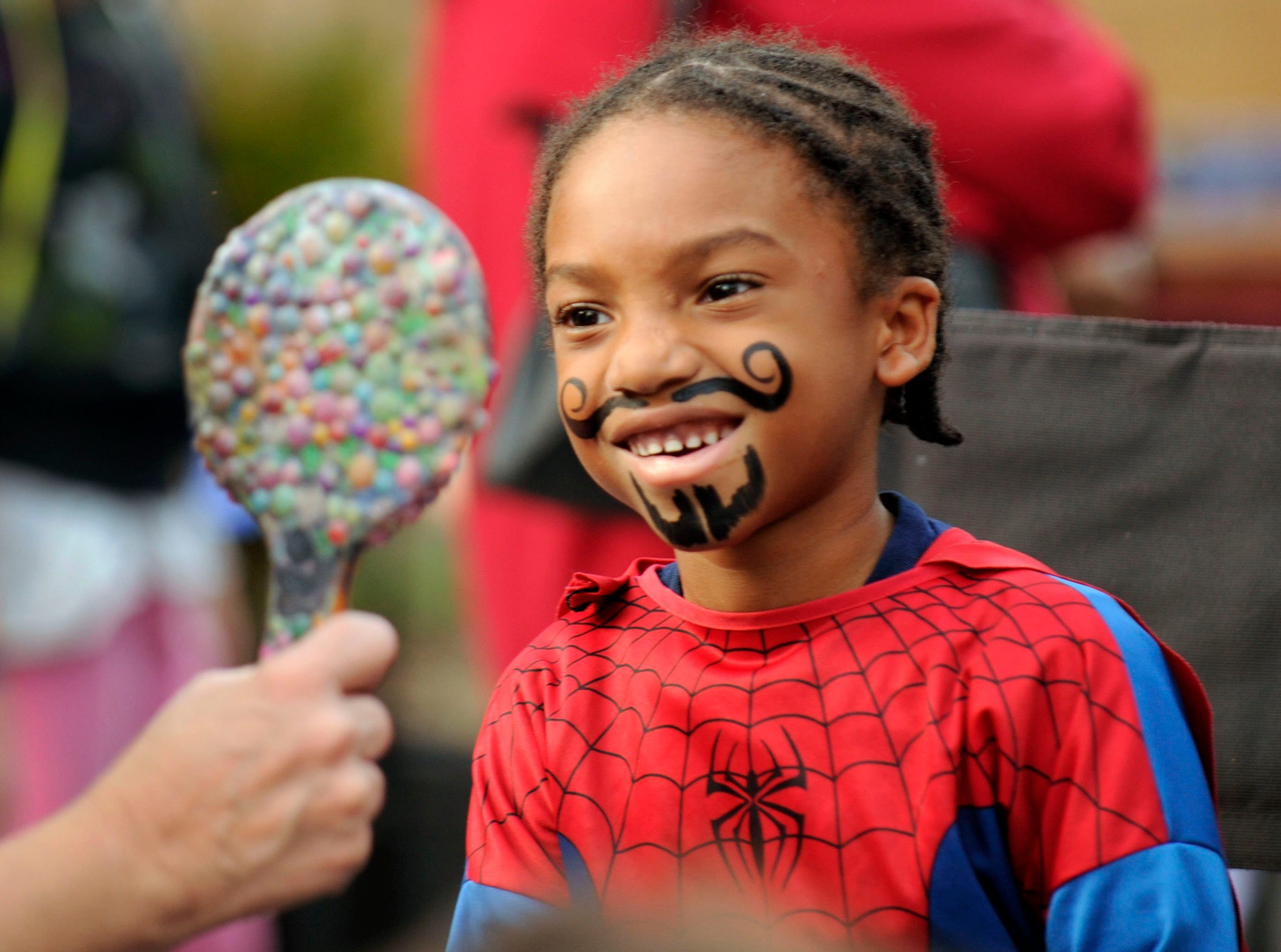Pierre Rogers, 6, grimaces at his own reflection after getting a face painted mustache during Halloween activities at the Boys and Girls Club Vestal in Knoxville on Wednesday, Oct. 30, 2013. Pierre attended the event with his mother Brittany Rucker.