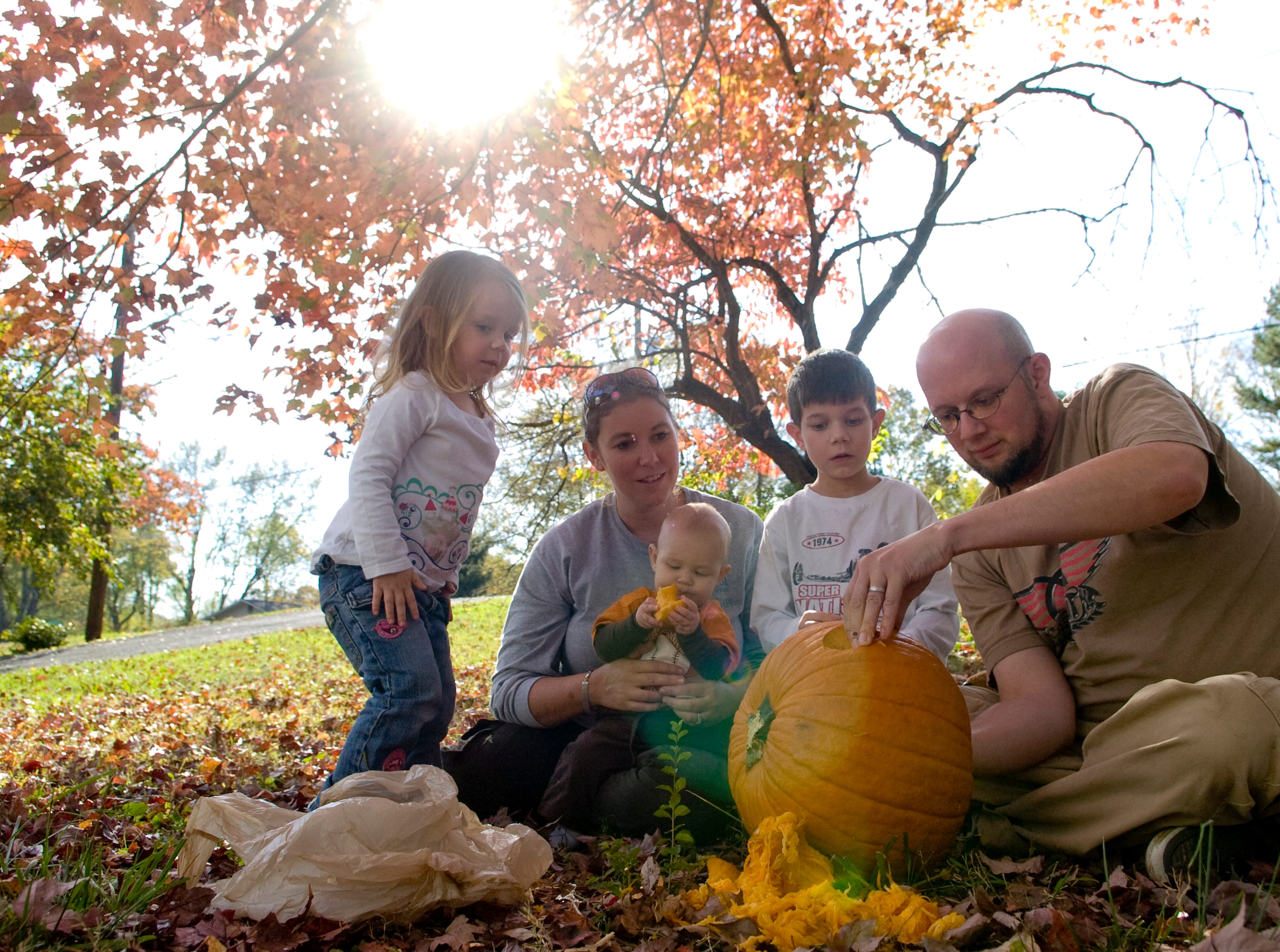The Schultz family, from left, Emma, 3, Melanie, Zachary, 7 months, Matthew, 6, and Christopher carve a pumpkin in their yard on Halloween day on Sunday, October 31, 2010.