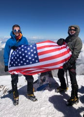 Isabella de la Houssaye, right, and her son stand atop Mount Elbrus, the tallest mountain in Europe, in July.