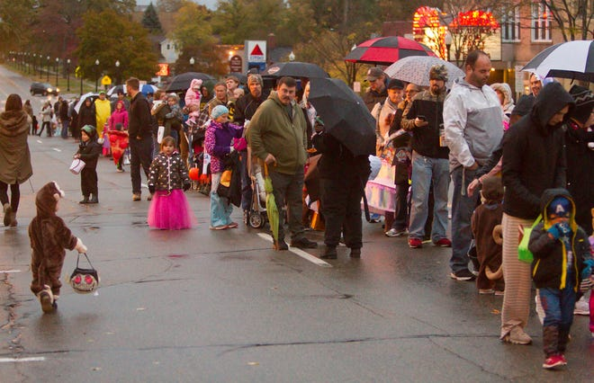Parents and trick-or-treaters form lines down Grand River Ave. in downtown Howell Saturday, Oct. 27, 2018 to receive goodies from local merchants during the annual The Legend of Sleepy Howell. This year's event will be a drive-thru experience, due to the pandemic.