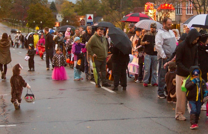 Parents and trick-or-treaters form lines down Grand River Ave. in downtown Howell Saturday, Oct. 27, 2018 to receive goodies from local merchants during the annual Legend of Sleepy Howell.