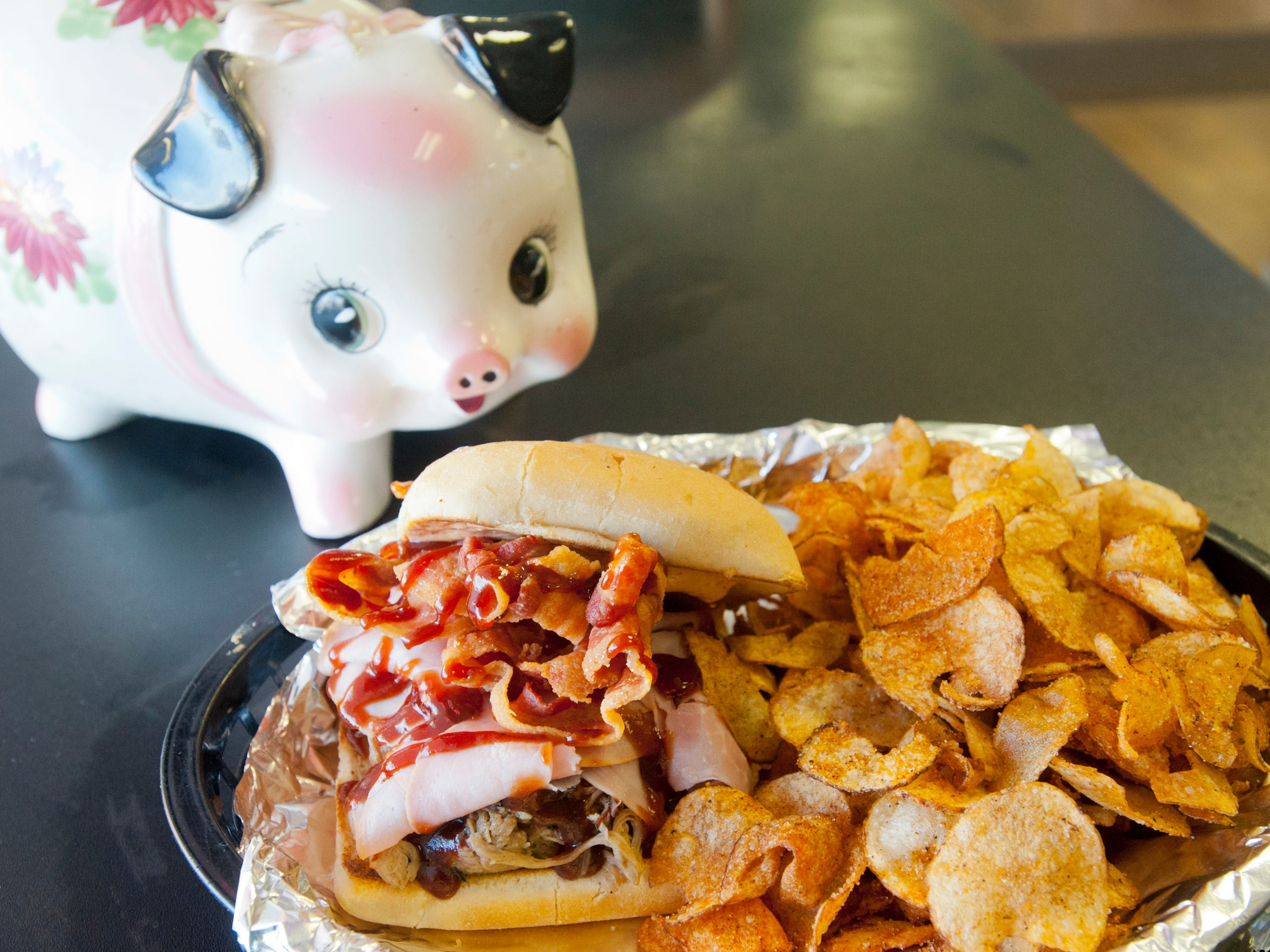 "Babie Bac'z Good Grill's Bac'z Attack sandwich is made with deep fried smoked bacon and pulled pork on a chiabbata bun topped with the eatery's original barbecue sauce. The dish is served with ""Shut Your Mouth"" potato chips that have been flavored with the restaurant's home-made dry rub.