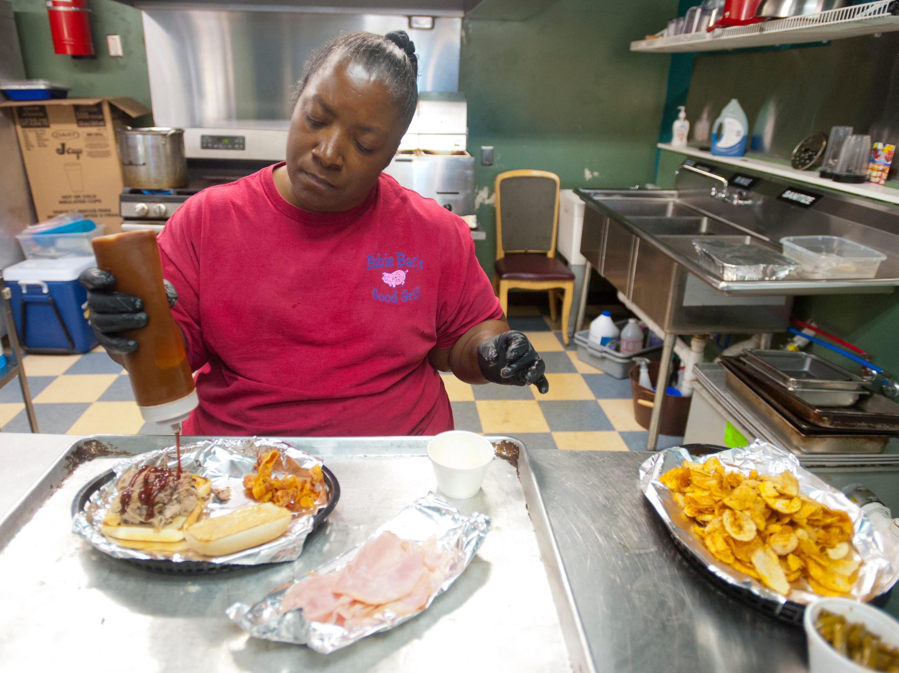 Babie Bac'z Good Grill co-owner Lydia Russell squirts some of the restaurant's original barbecue sauce on the eatery's Bac'z Attack sandwich made with deep fried smoked bacon and pulled pork on a chiabbata bun.