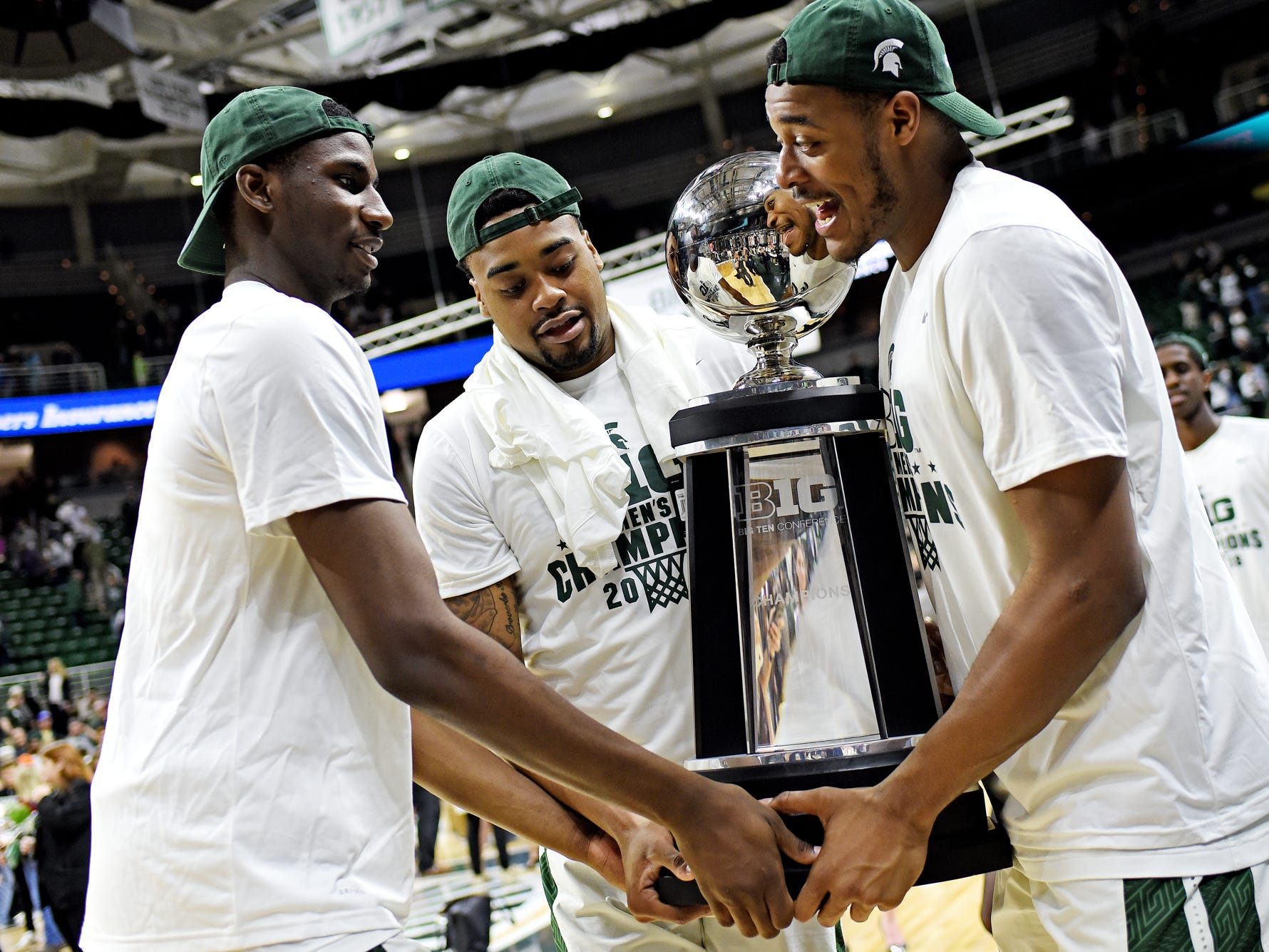 From left, Michigan State's Jaren Jackson Jr., Nick Ward and Xavier Tillman carry the BIG 10 Conference championship trophy back to the locker room after the game on Tuesday, Feb. 20, 2018, at the Breslin Center in East Lansing. The Spartans beat Illinois 81-61.