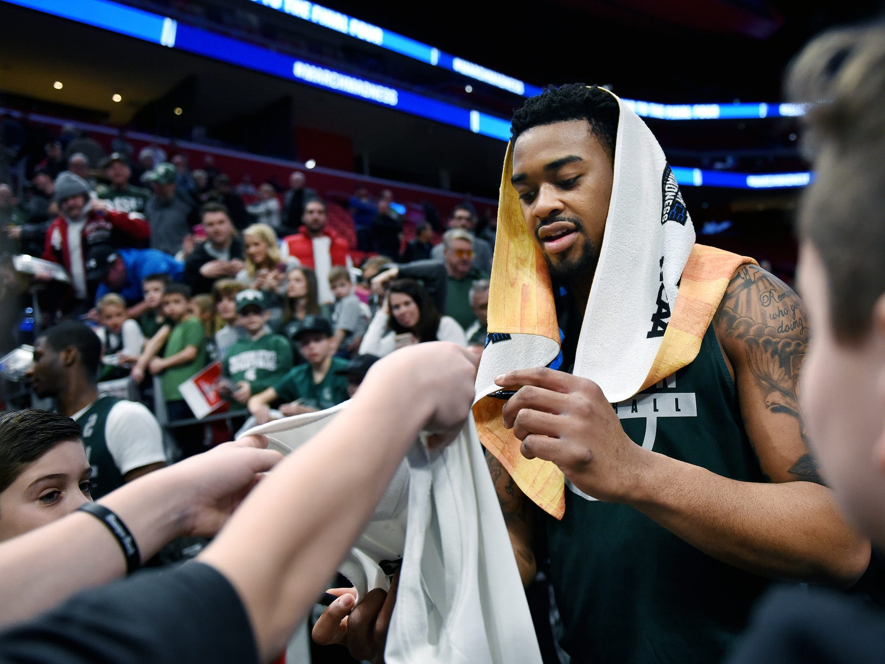 Michigan State's Nick Ward signs autographs for fans at the end of an open practice on Thursday, March 15, 2018, at the Little Caesars Arena in Detroit.