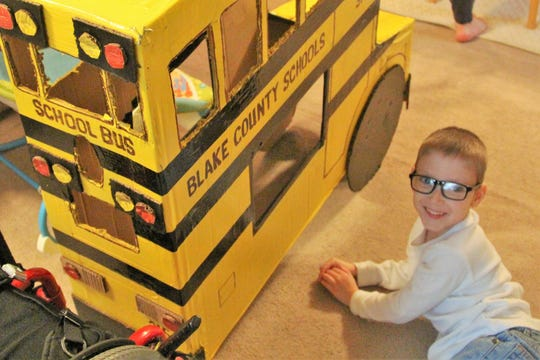 Blake Mompher, 5, lays next to his school bus Halloween costume that fits over his wheelchair. Mompher has spina bifida.