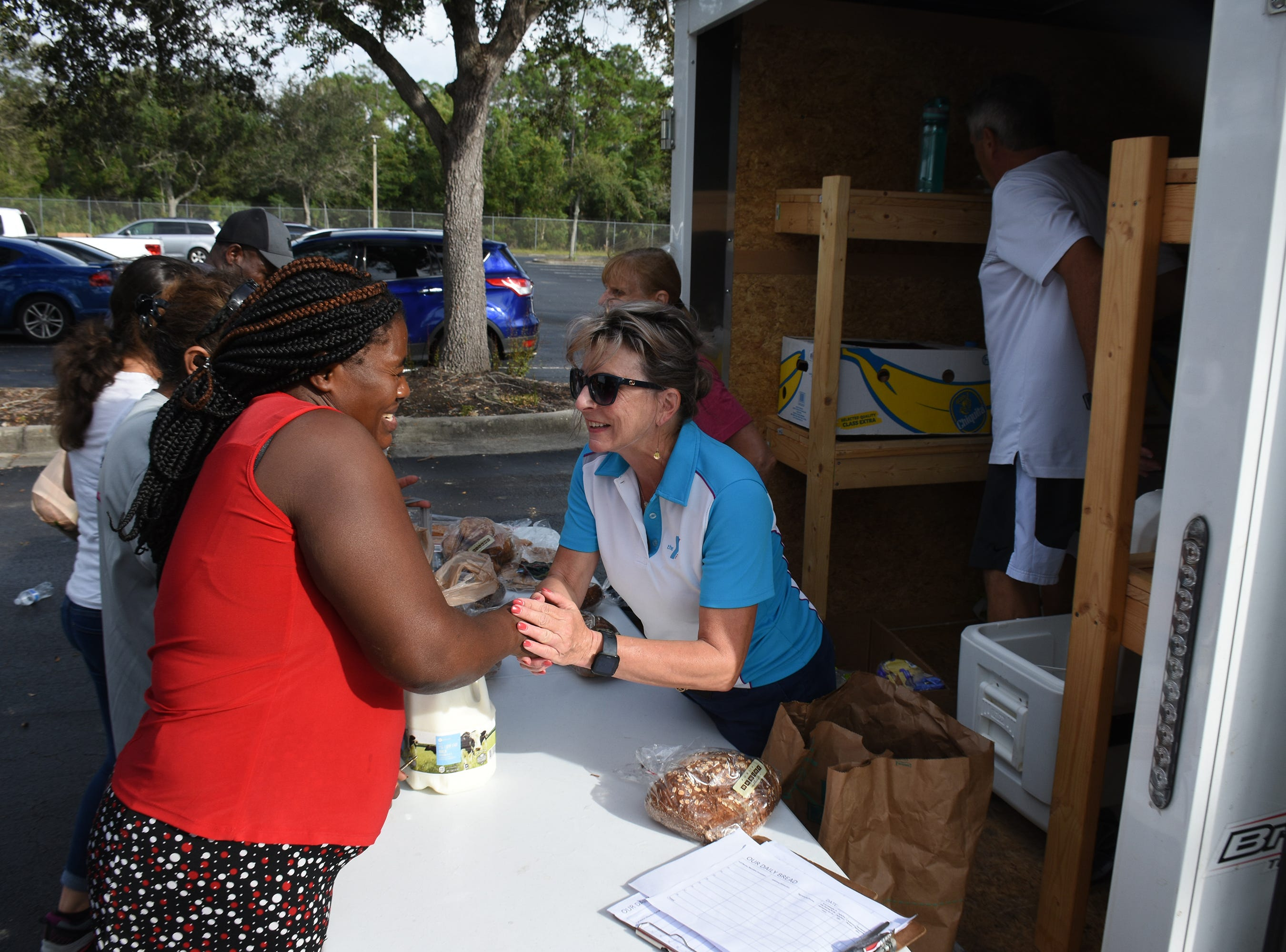 Allyson Richards, right, greets a client and asks about her family. A group of Marco Island volunteers conducts a food pantry Friday afternoon at Manatee Middle School.