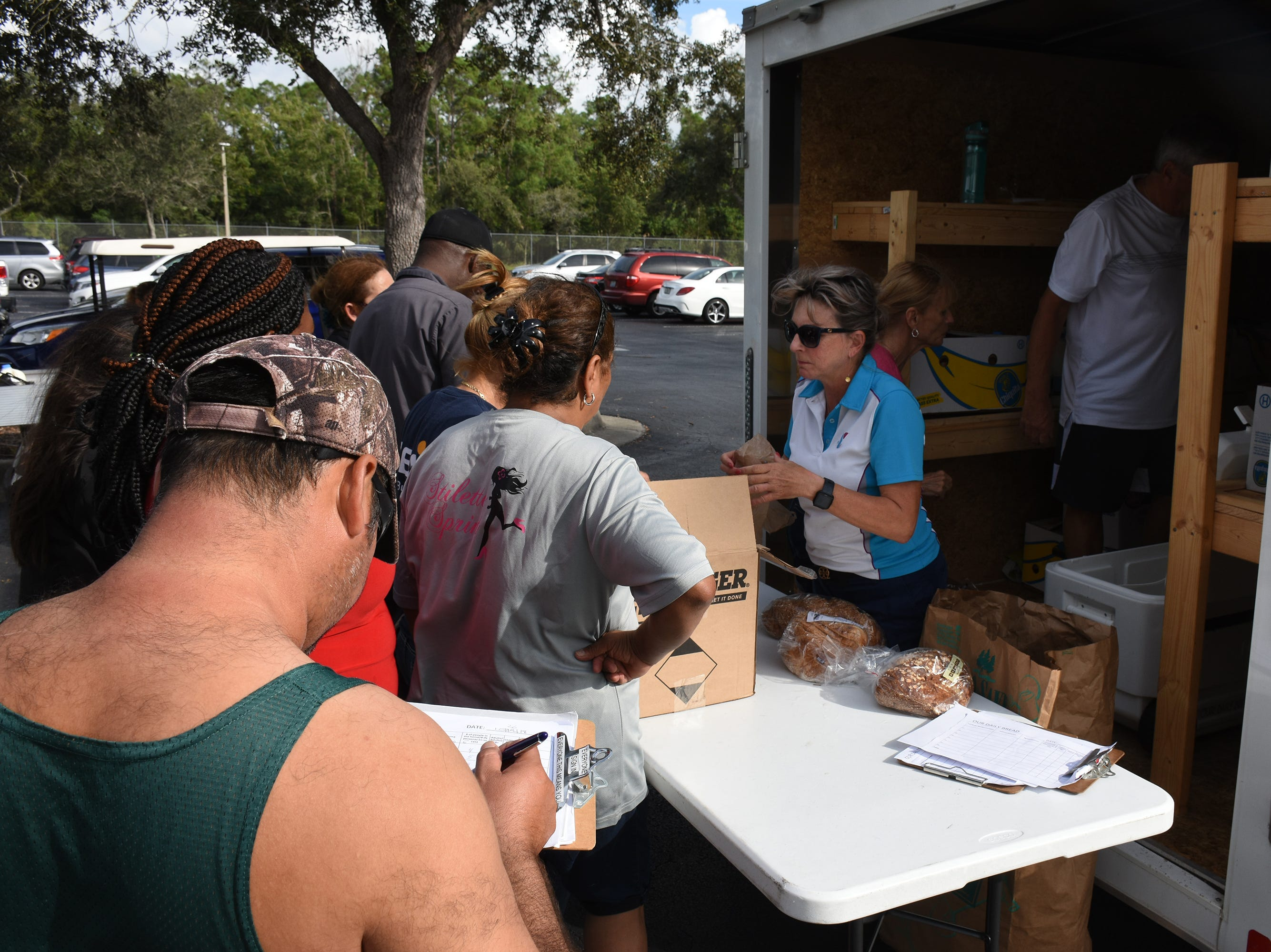 Allyson Richards, right, greets a client as another fills out a simple form. A group of Marco Island volunteers conducts a food pantry Friday afternoon at Manatee Middle School.