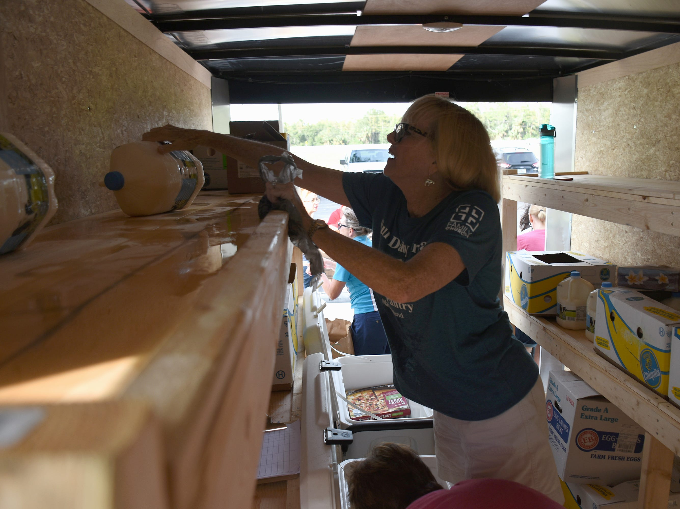 Patti Porter pulls more supplies out of the food pantry trailer. A group of Marco Island volunteers conducts a food pantry Friday afternoon at Manatee Middle School.