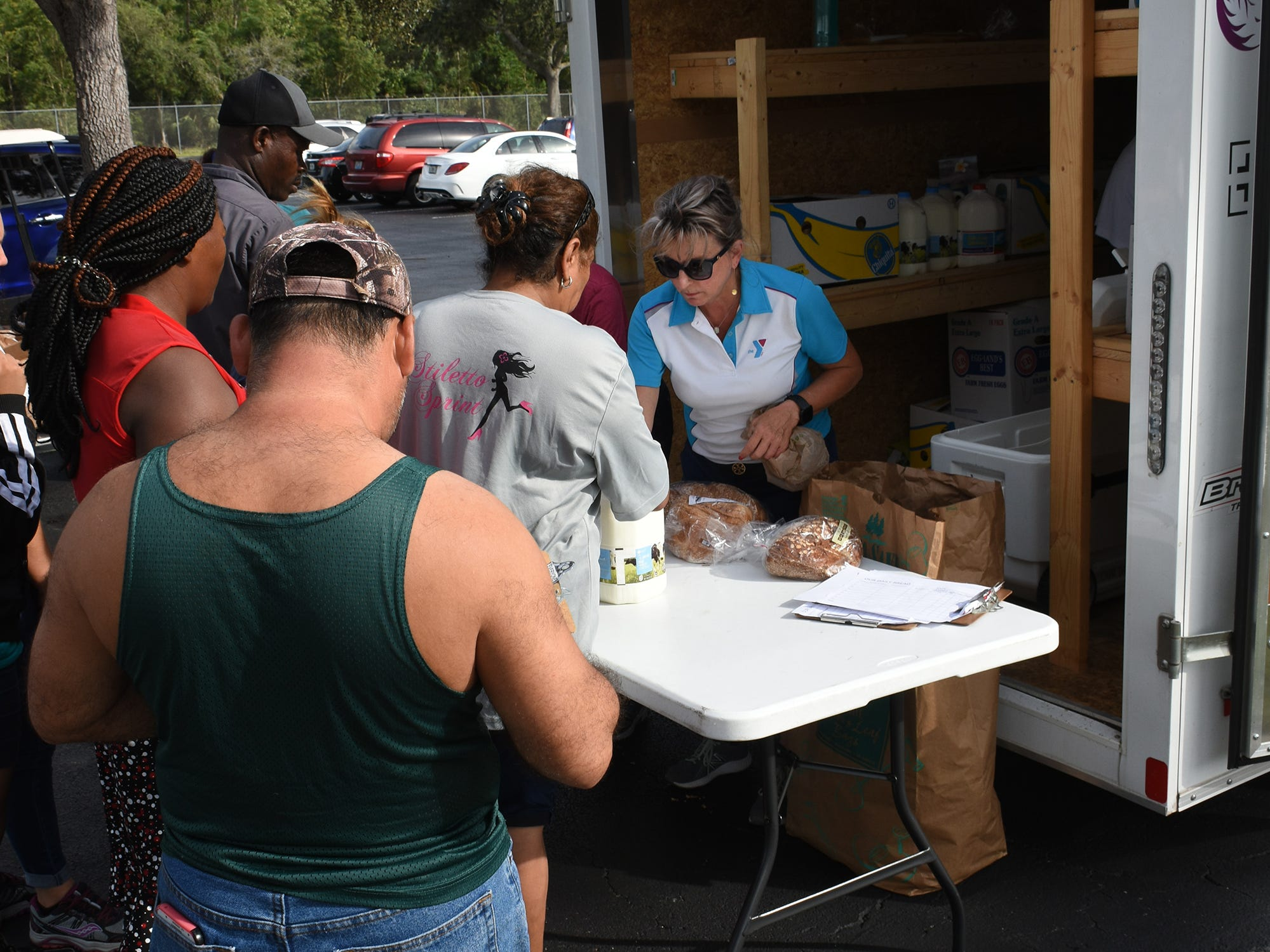 Allyson Richards, right, welcomes clients to the pickup. A group of Marco Island volunteers conducts a food pantry Friday afternoon at Manatee Middle School.