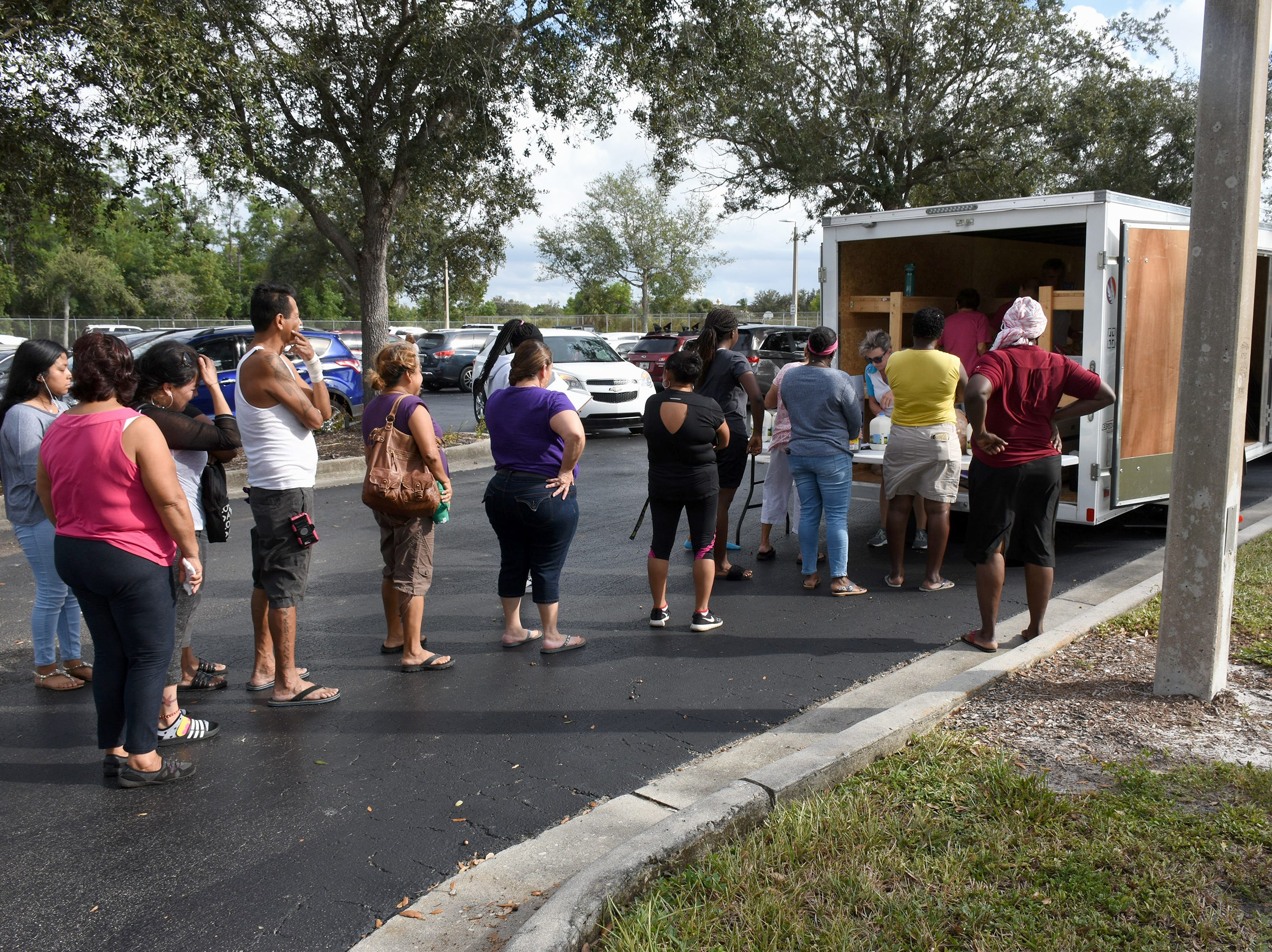 Families line up to receive food donations. A group of Marco Island volunteers conducts a food pantry Friday afternoon at Manatee Middle School.