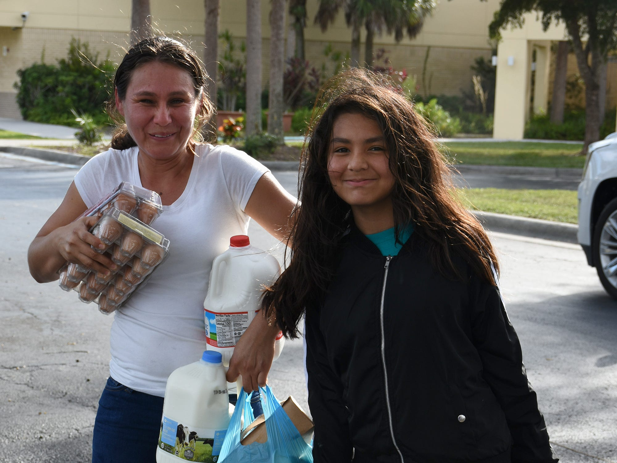 Erica Gutierrez, 11, and her mom Erica head out with their groceries. A group of Marco Island volunteers conducts a food pantry Friday afternoon at Manatee Middle School.