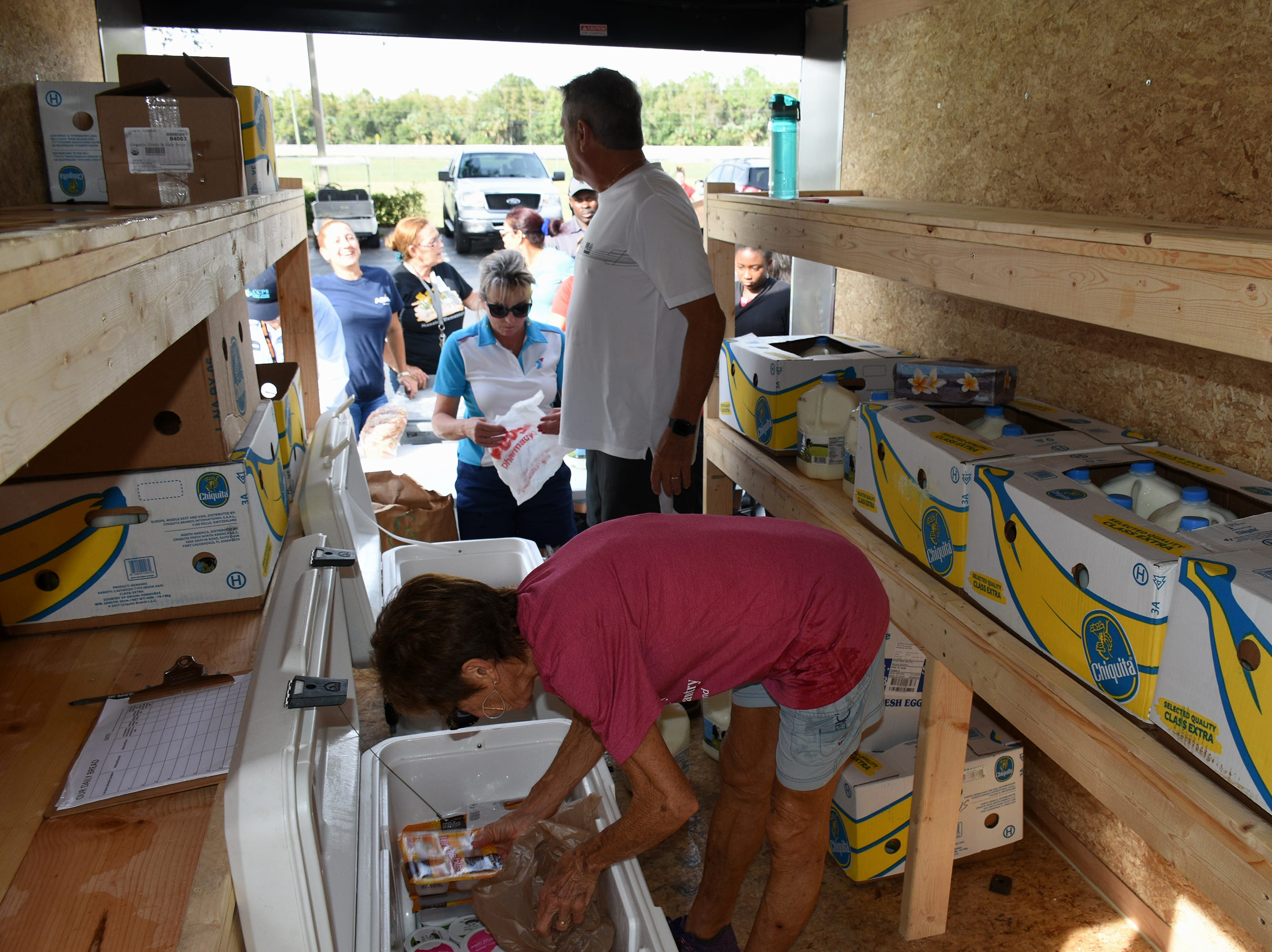 Tricia Simmler pulls more supplies out of the food pantry trailer. A group of Marco Island volunteers conducts a food pantry Friday afternoon at Manatee Middle School.