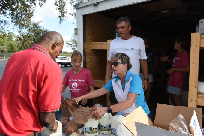 Allyson Richards, right, greets a client as he collects food items. A group of Marco Island volunteers conducts a food pantry Friday afternoon at Manatee Middle School.