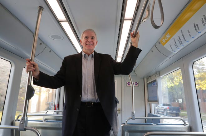 Milwaukee Mayor Tom Barrett stands in the streetcar's general seating section during the Milwaukee streetcar test ride.