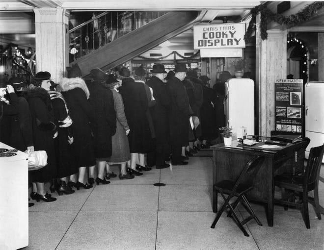 Customers stand in line to see the cookie display and get their copy of the electric company's cookie book in 1938. The 2018 edition will be given away by We Energies Saturday at Miller Park.