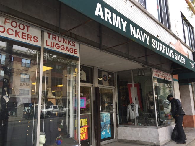 A man looks in the window of Army & Navy Surplus Sales, 707 W. Wisconsin Ave. The store, which has been in business for nearly 50 years, is closing.