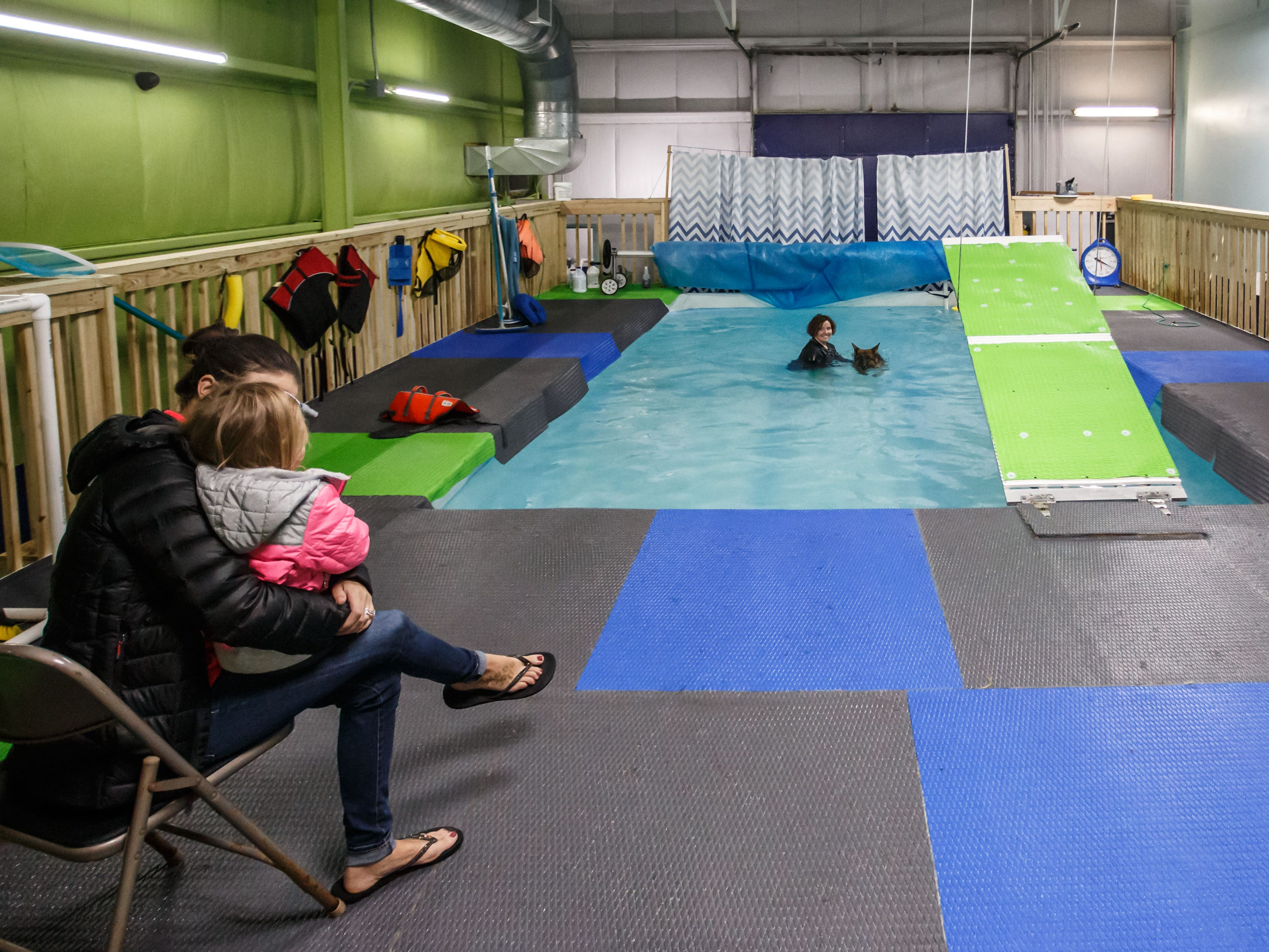 Brittany Ottow and her daughter Addison, of Hartford, look on as owner/trainer Becky Pease works with their German Shepherd in the indoor heated dog pool at Aqua Therapups in Slinger on Monday, Oct. 29, 2018.