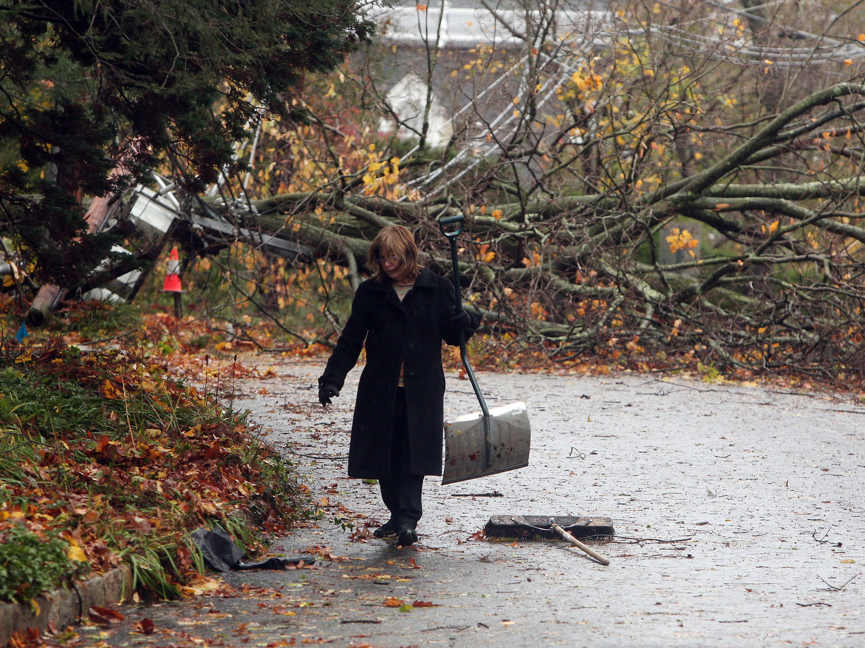 Morristown, NJ-- October 30, 2012--Pat Podell of Morristown, NJ clears the street of fallen leaves on Ogden Street in the aftermath of Hurricane Sandy. 