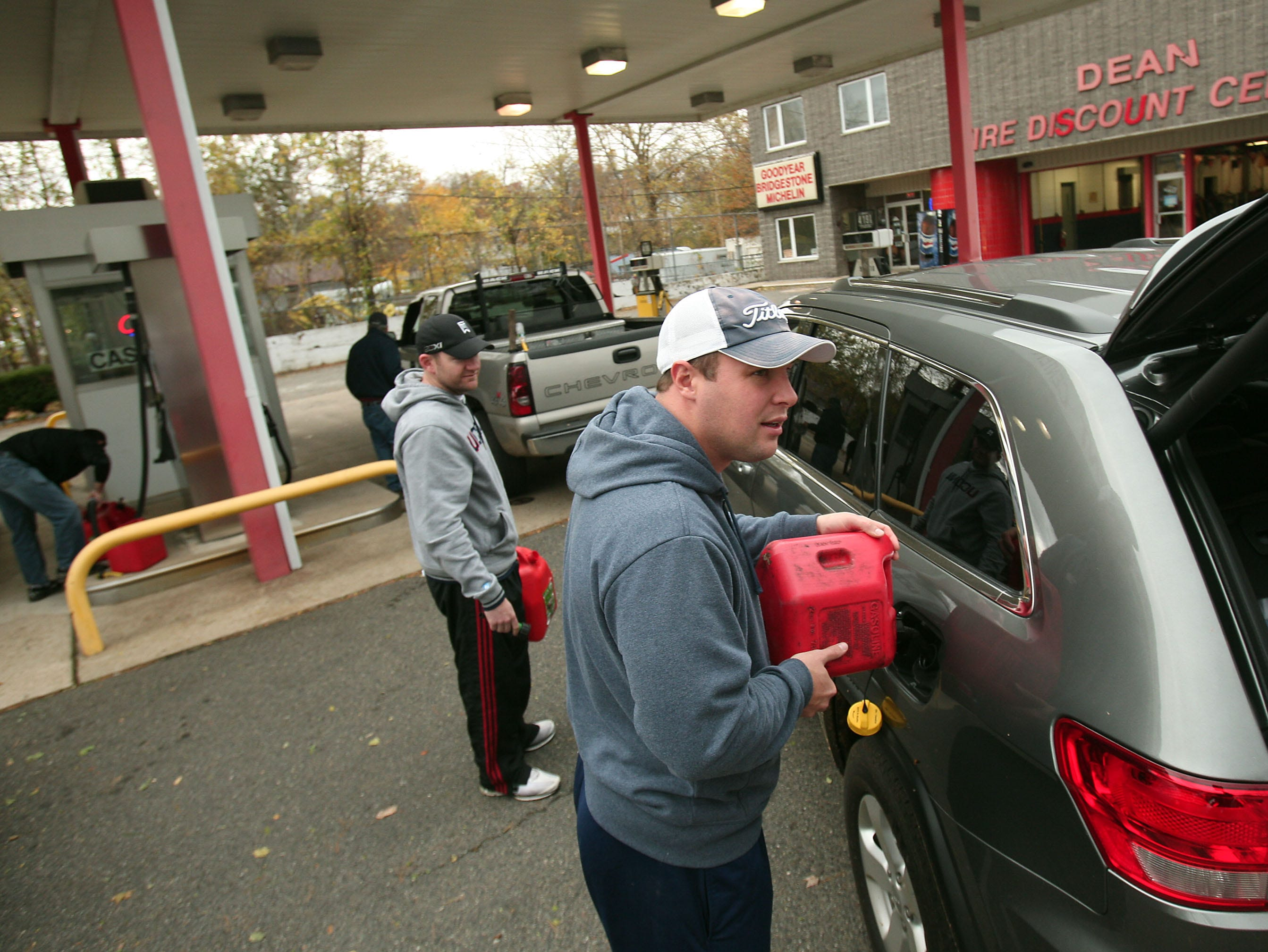 Morristown, NJ-- October 31, 2012--Tom Collins of Morristown, NJ puts gas in his SUV. Collins waited over 45 minutes to fill up his tank and gas cans at Dean Discount Center in Morristown in the aftermath of Hurricane Sandy. 