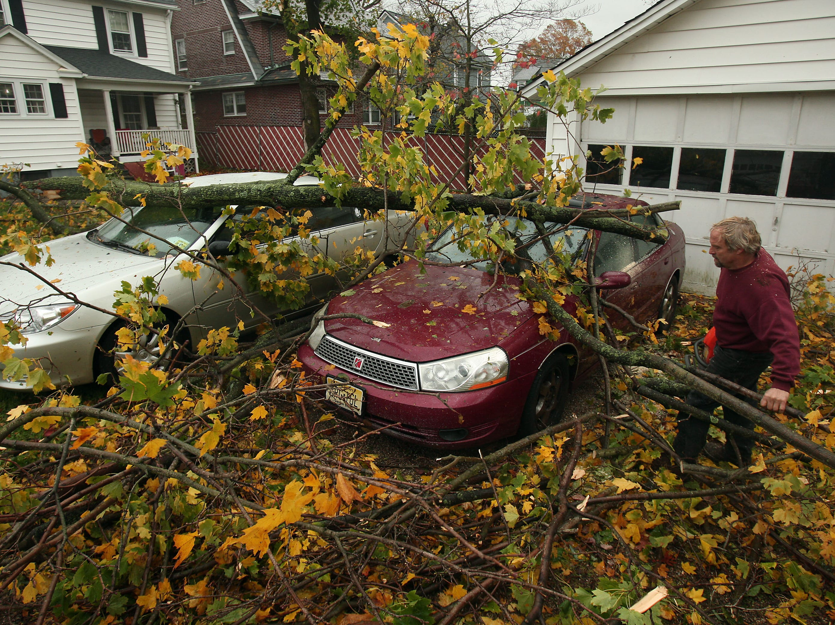 Morristown, NJ-- October 30, 2012--Steve Penzenik Sr. of Roxbury cleans up fallen branches on Mills Street in Morristown, NJ after Hurricane Sandy left homes damages and without power throughout New Jersey. 