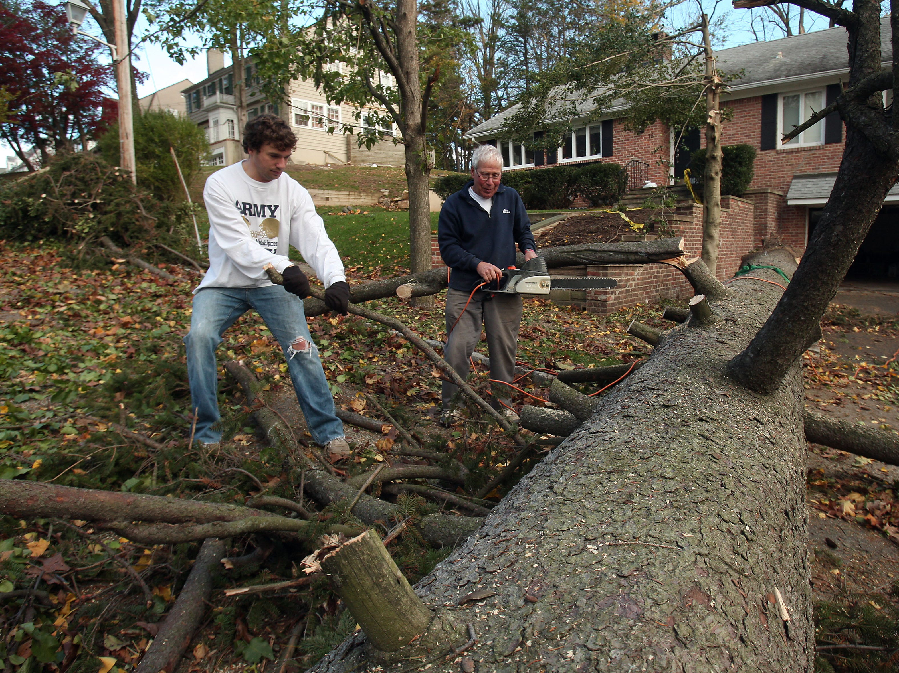 Morristown, N.J.- November 3, 2012--Carl Harter, l, and his fatherJohn of Chatham, NJ help to clear a giant tree that fell from Carl's front yard across Tuxedo Lane in Morristown, NJ as local recovery continues in the aftermath of Hurricane Sandy.Bob Karp/Staff Photographer/DAILY RECORD