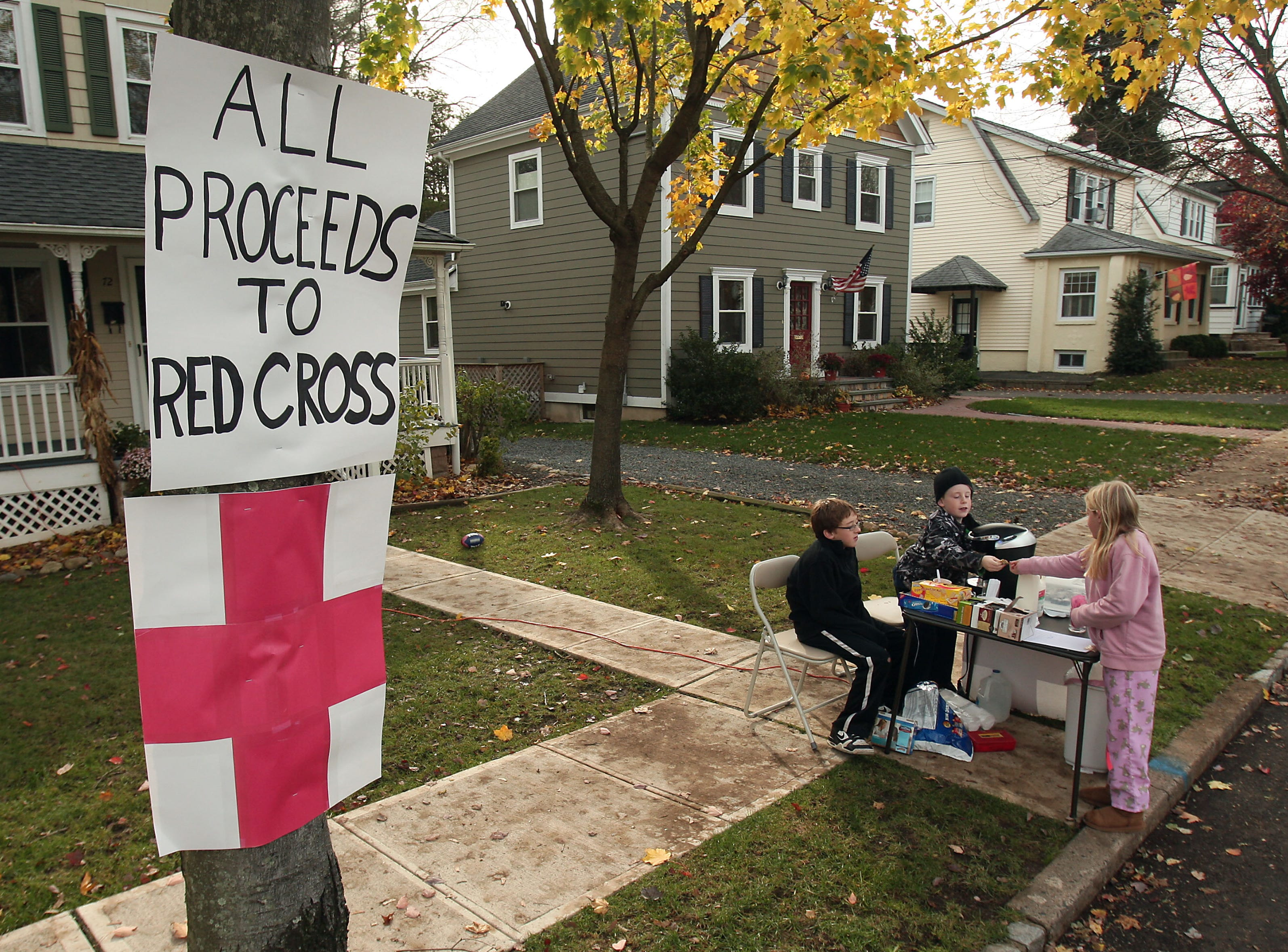 Chatham, NJ- November 1, 2012--9-year-old Hannah Leroux of Chatham, NJ makes a donation to Nick Meyer (11) and Jack Konrad (8) who are collecting proceeds for the Red Cross on Hedges Avenue as locals continue the recovery process after Hurricane Sandy devastated the eastern seaboard.